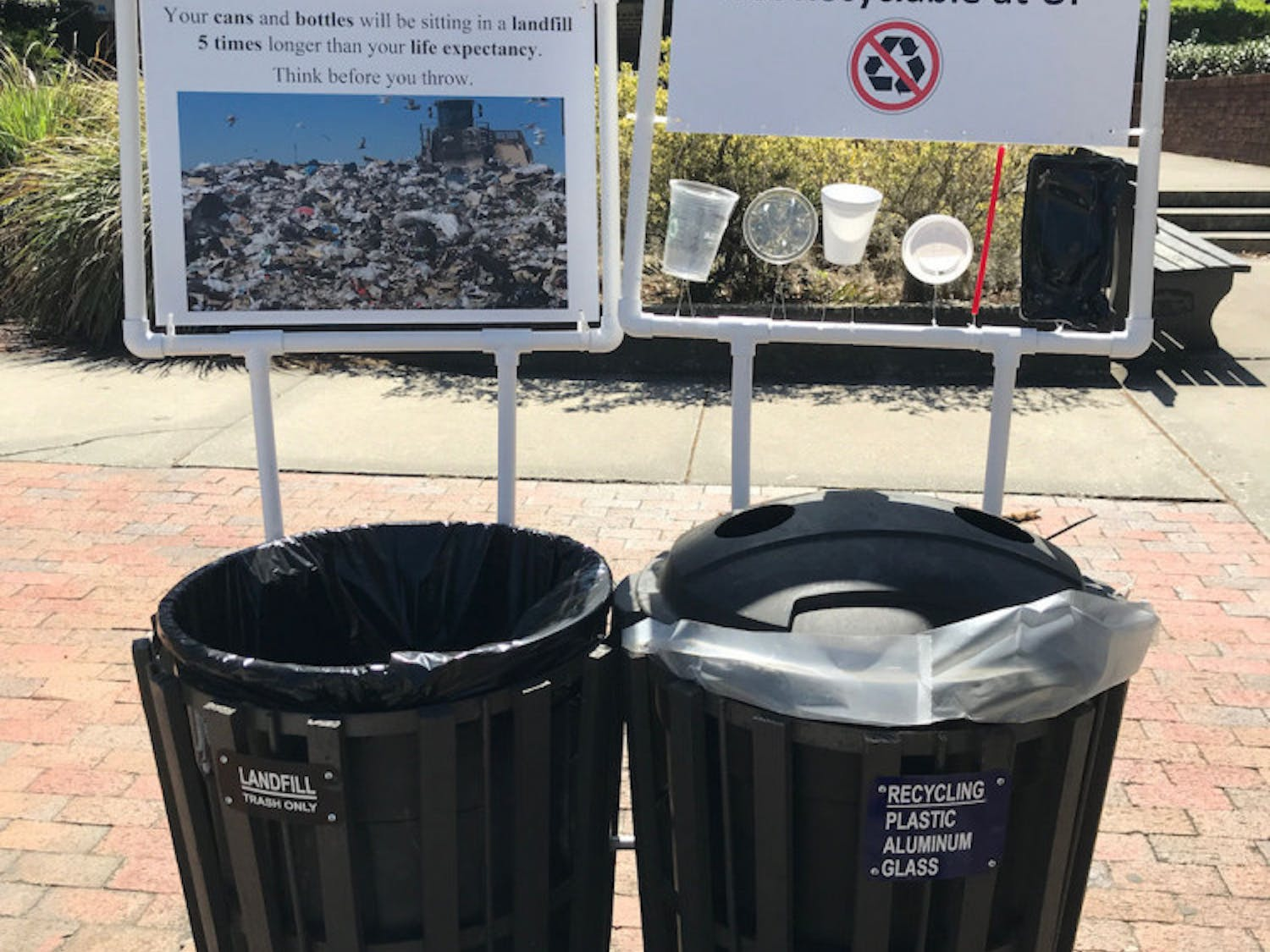 Pictured is a pair signs framed by PVC pipes hanging next to a set of trash and recycling cans that appeared on campus early Monday morning. The signs are part of a student research project by UF/IFAS first-year PhD student Amanda Brinton. The signs will be up until April 20, she said.