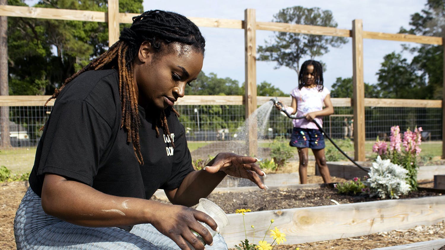 Kimberly Brown, 30 (left), sprinkles fertilizer around newly planted daises as her 7-year-old daughter, Bella Smith (right), waters a garden plot behind her on Monday, March 29, 2021. They spent the day at Reserve Park for the second Gainesville Black Garden Network meeting since the group formed in February.
