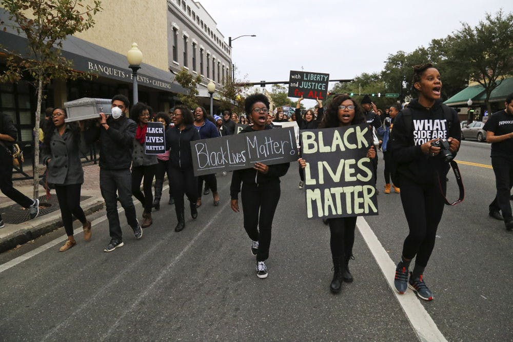 <p>Protesters for the #BLACKLIVESMATTER march walk west on University Avenue on Monday afternoon.</p>