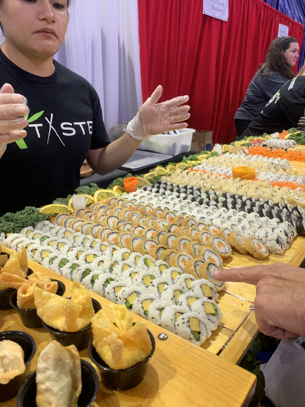<p>Taste of Greater Gainesville attendees samples sushi provided by Taste, a local restaurant that serves Pan-Asian cuisine.</p>