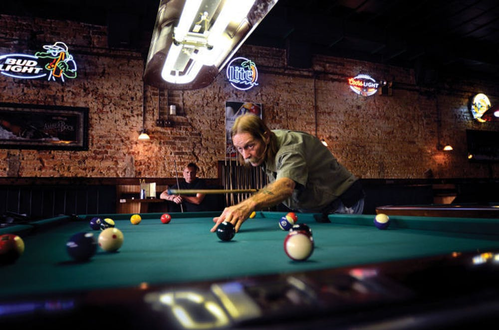 "<p>""Doctor"" Robert Ramsthaler takes a shot during a game of pool as Tom Miller, the first official billiard therapy patient, watches Sept. 16 at Main Street Bar &amp; Billiards.</p>"