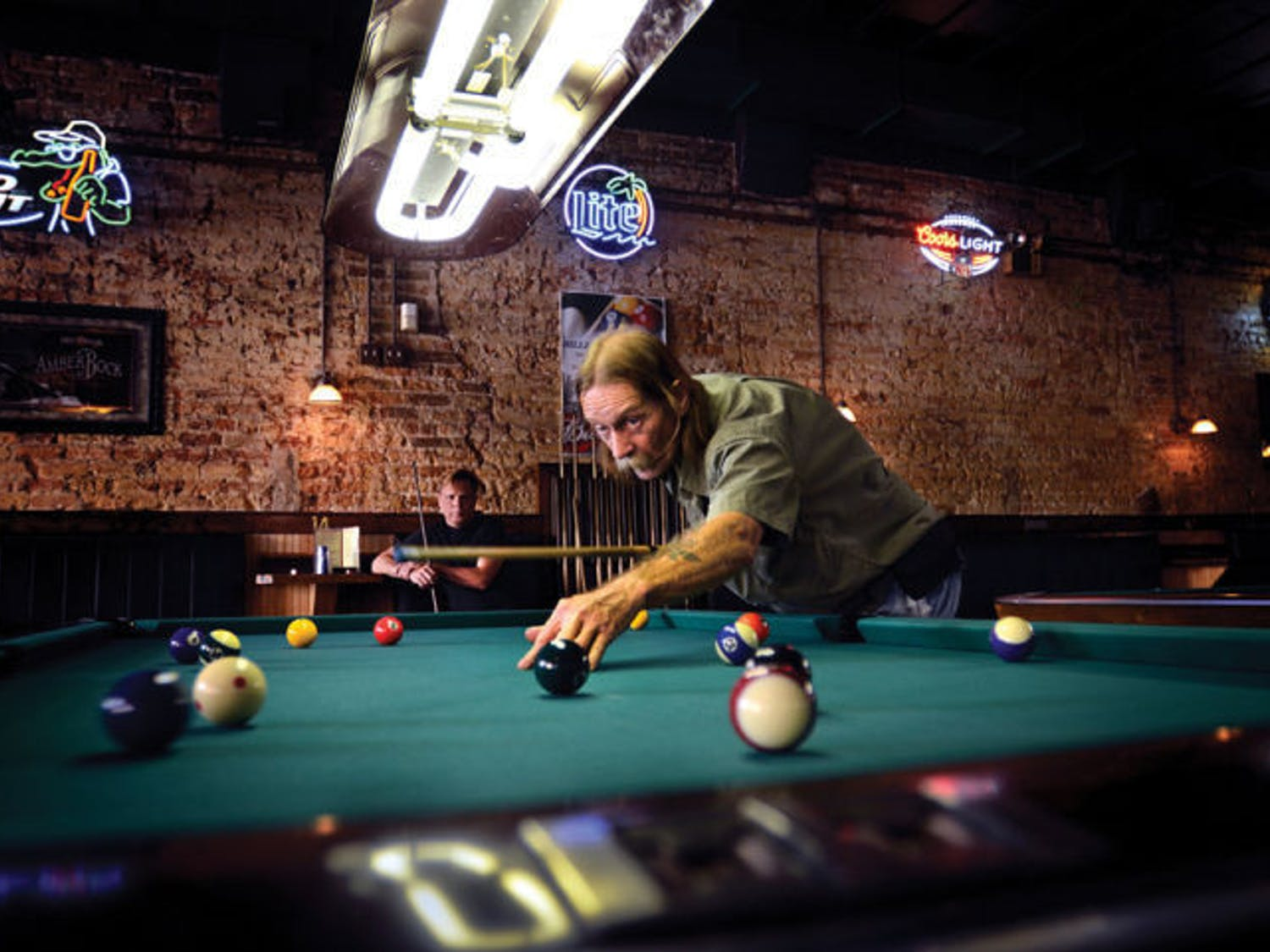"""""""Doctor"""" Robert Ramsthaler takes a shot during a game of pool as Tom Miller, the first official billiard therapy patient, watches Sept. 16 at Main Street Bar & Billiards."""