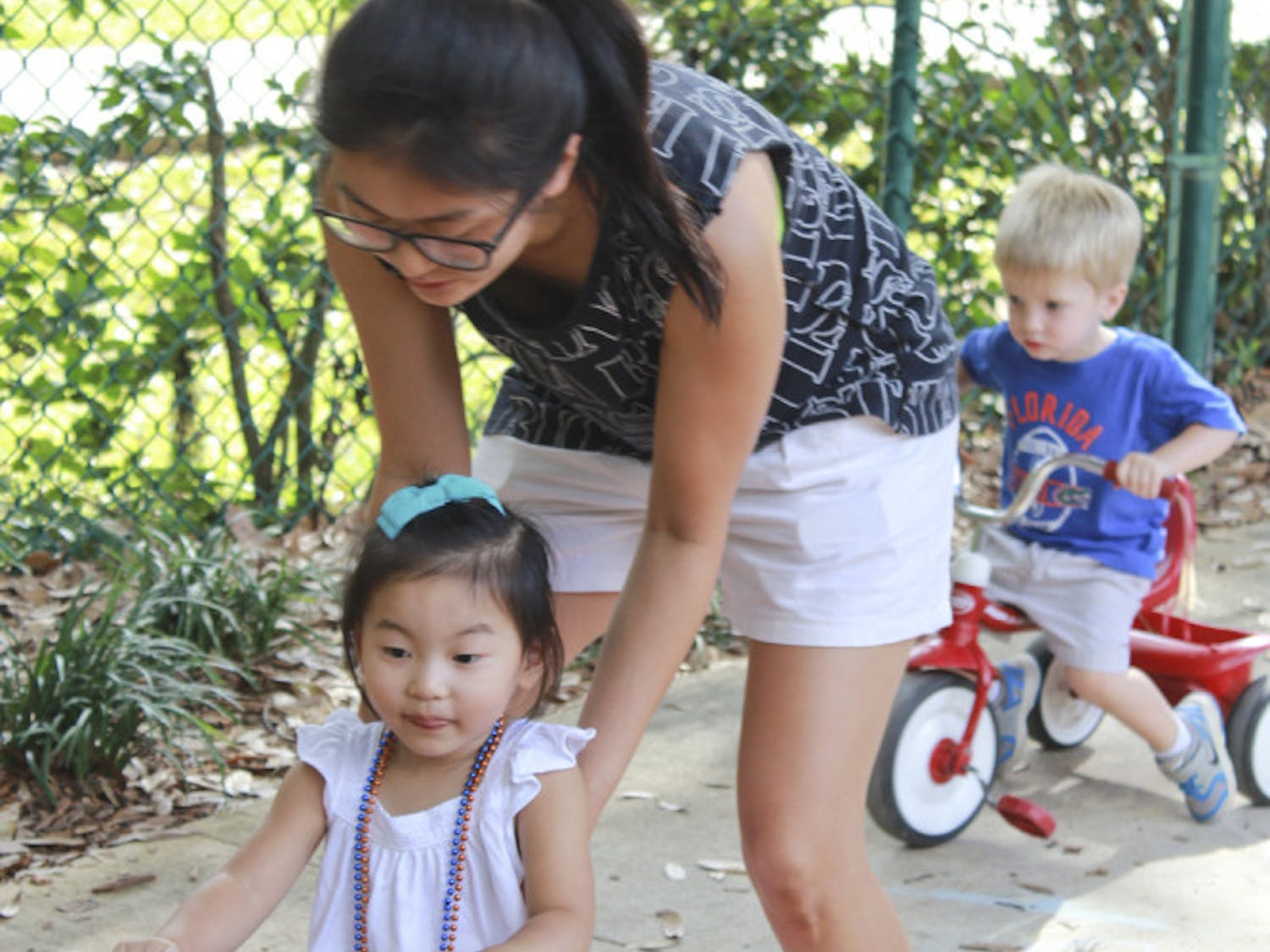 Former UF PhD student Soon Hye Yang, 34, pushes her 3-year-old daughter, Isu Yoon, on a tricycle at the Baby Gator daycare center on Nov. 5, 2015. Baby Gator's request for additional funding was denied, and without it, student parents like Yang may be cut from the program.