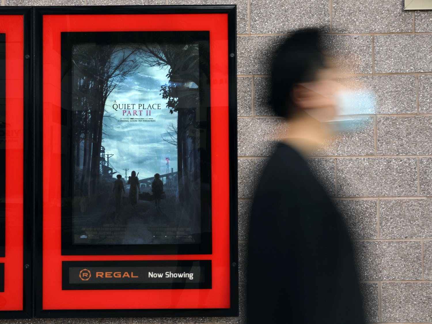 """Haoxian Li, 24, an Orlando resident, walks past a movie poster for """"A Quiet Place Part II"""" at Regal Celebration Pointe theater in Gainesville on Thursday, June 3, 2021."""