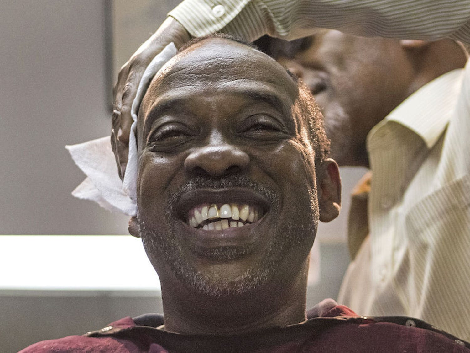 Vincent Tate, 51, receives a haircut Tuesday from Edward Young, 64, at the Clean Cut Barber Shop on Northwest Fifth Avenue. Tate moved from Alabama to Gainesville for a fresh start, and he has worked for the Alachua County School Board for 25 years.