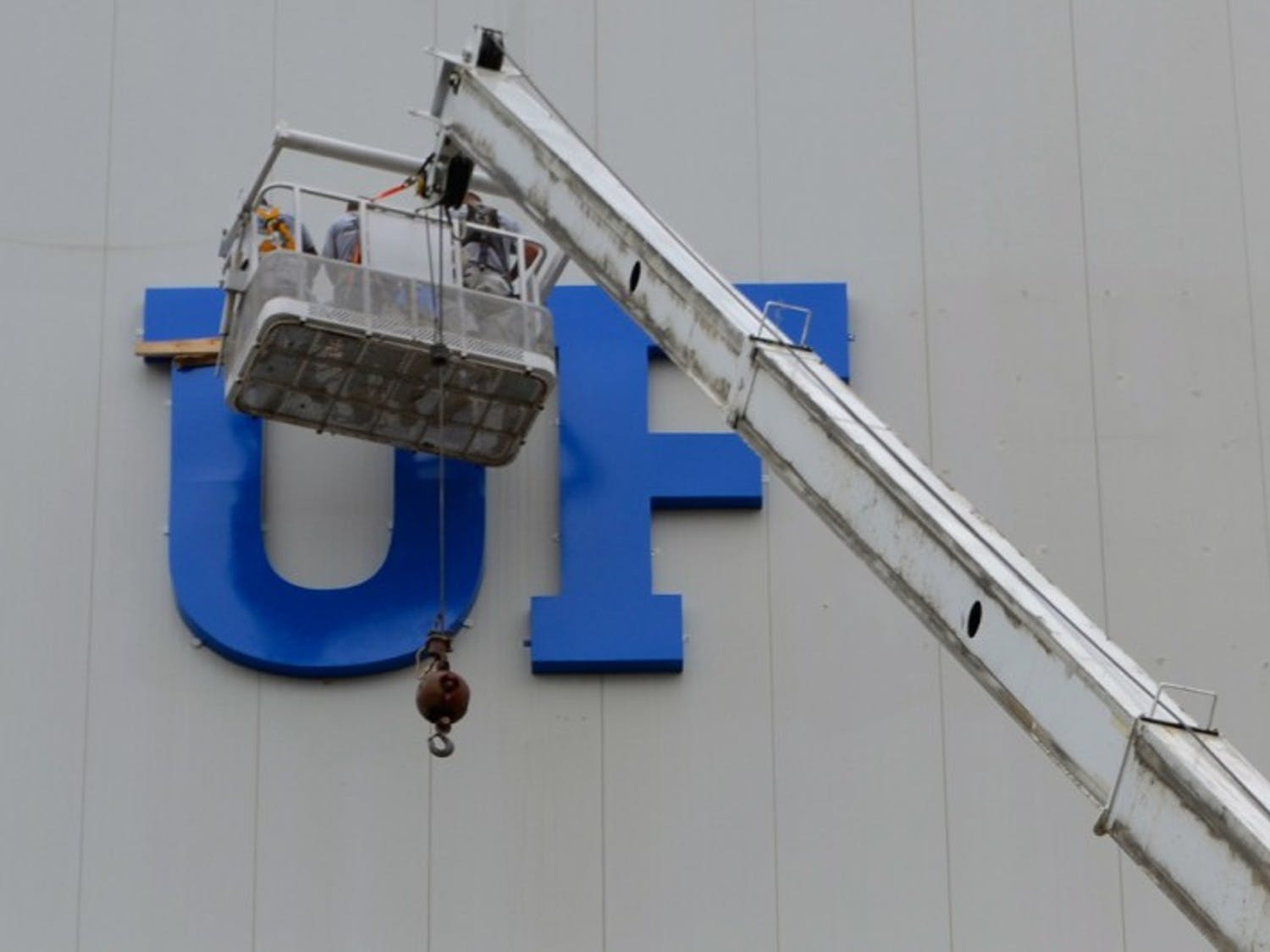 Rebranding - Construction workers hang a new sign on the southside of Ben Hill Griffin Stadium Thursday afternoon.