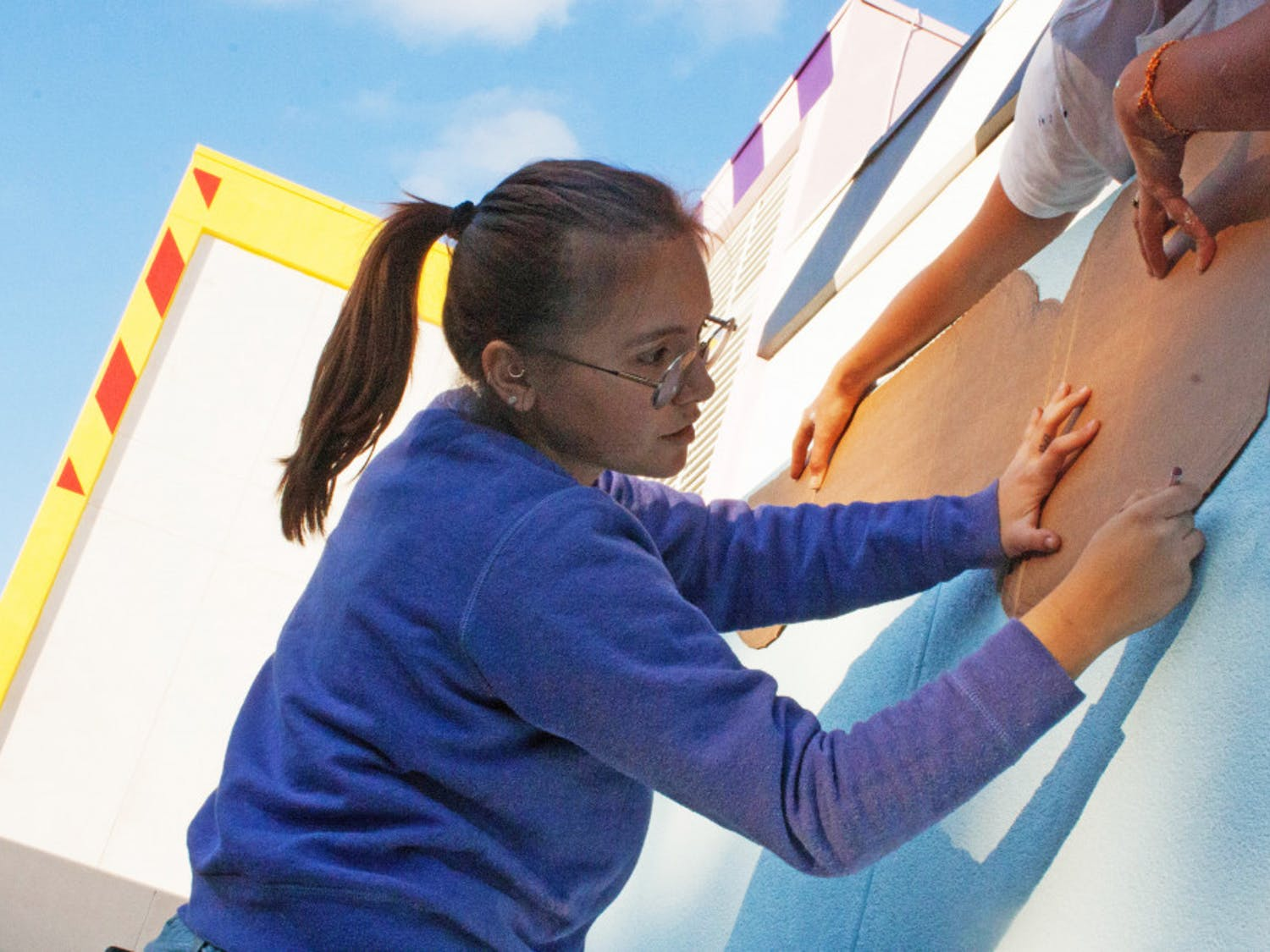 Jovana Christiani, a 19-year-old Santa Fe College illustration sophomore, outlines the new mural on Santa Fe's walls Tuesday. The mural is set to be finished Saturday.
