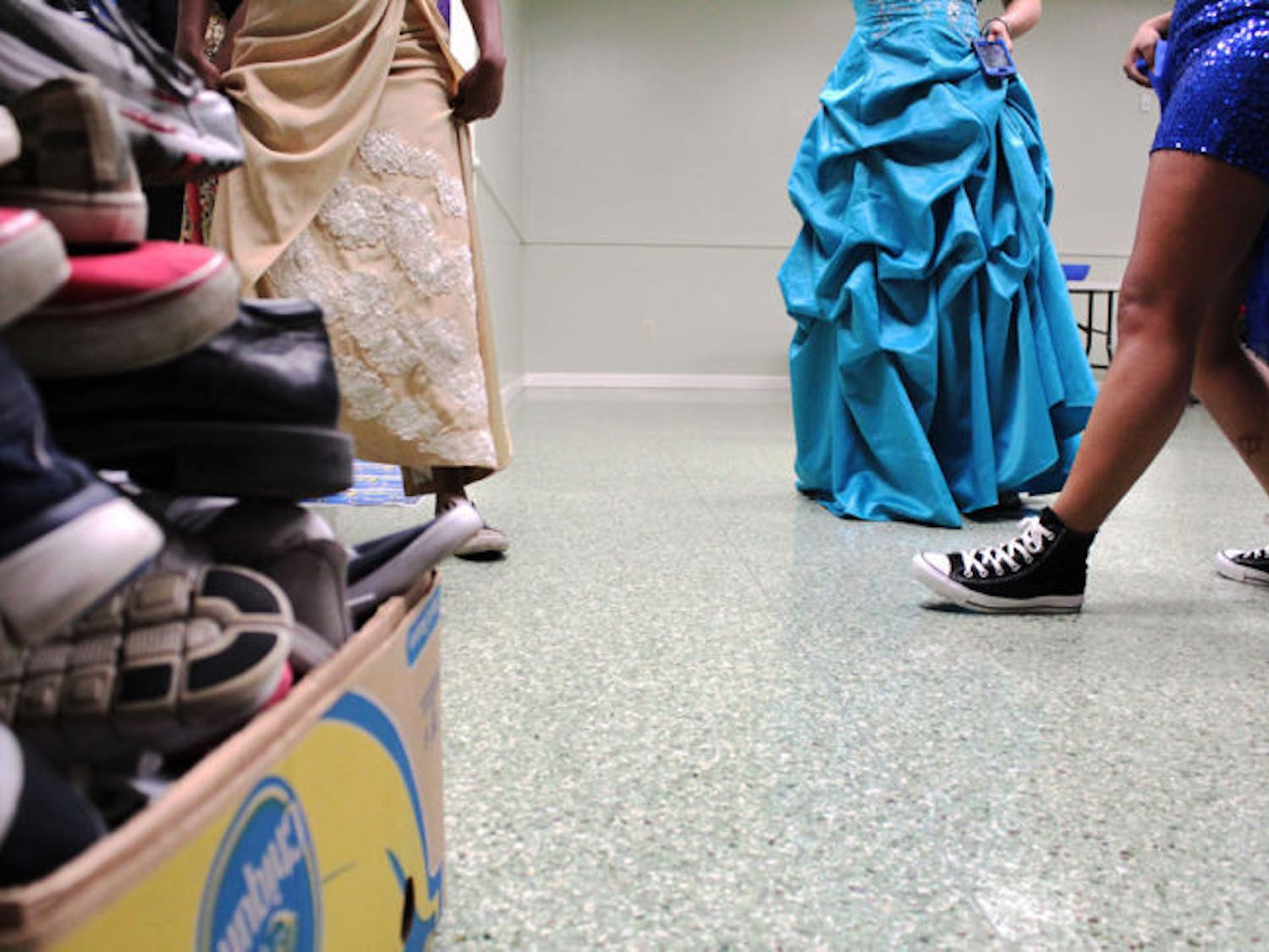 The members of the UF Lambda Rho chapter of Sigma Gamma Rho sorority wear sneakers to a formal dance on Saturday in the Broward Hall basement. The group collected $1,000 and about 100 pairs of sneakers for Soles4Souls and St. Francis House.