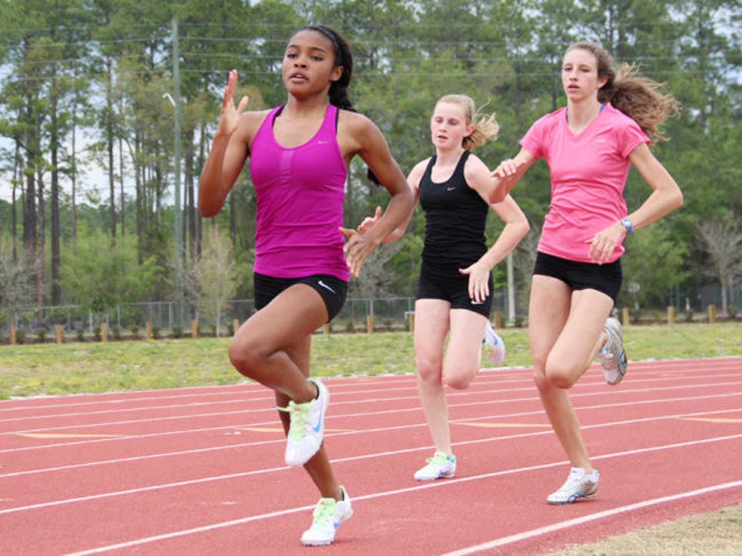 Three Eastside High School students run at Fred Cone Park, 2841 E. University Ave., during track practice on Monday afternoon.