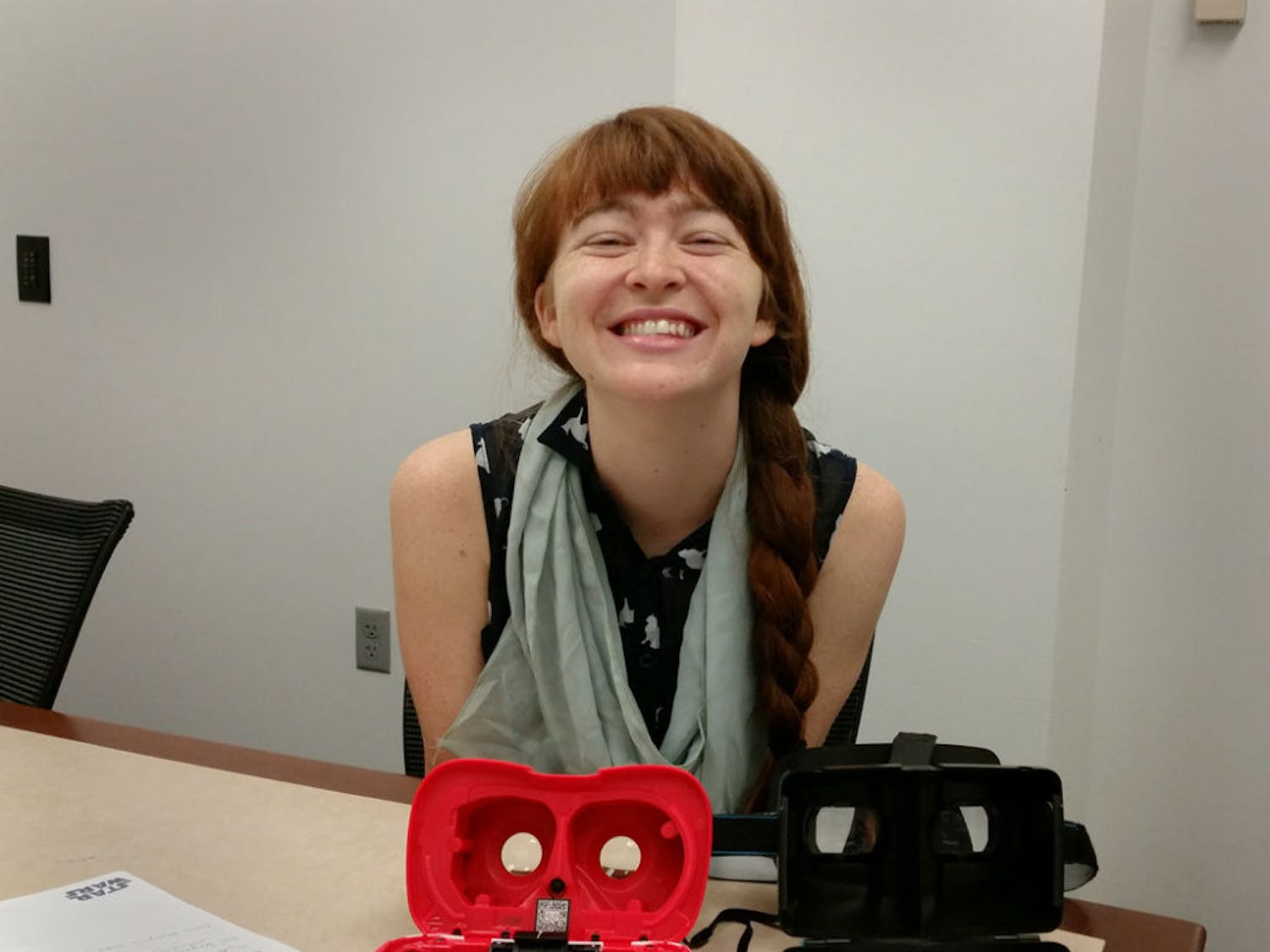 Caitlin Kearney, 23, a recent graduate of UF's Digital Arts and Sciences program, smiles for a photo with virtual reality headsets, which are used to play the smartphone puzzle game Newton's Dream.