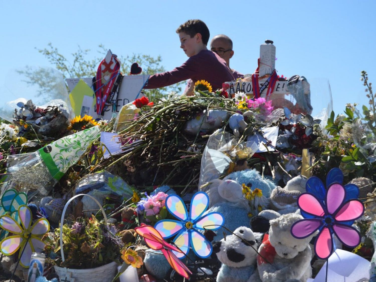A young boy lays down a flower at the victim's memorials outside Marjory Stoneman Douglas High School on March 3.