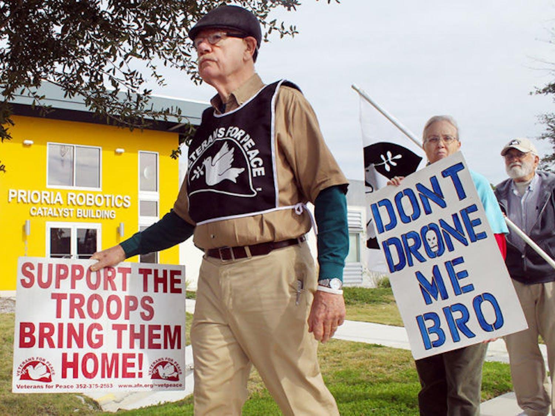 Veterans for Peace Vice President John Fullerton (left), 72, and retired social worker Miriam Elliot, 62, protest Wednesday outside of Prioria Robotics.