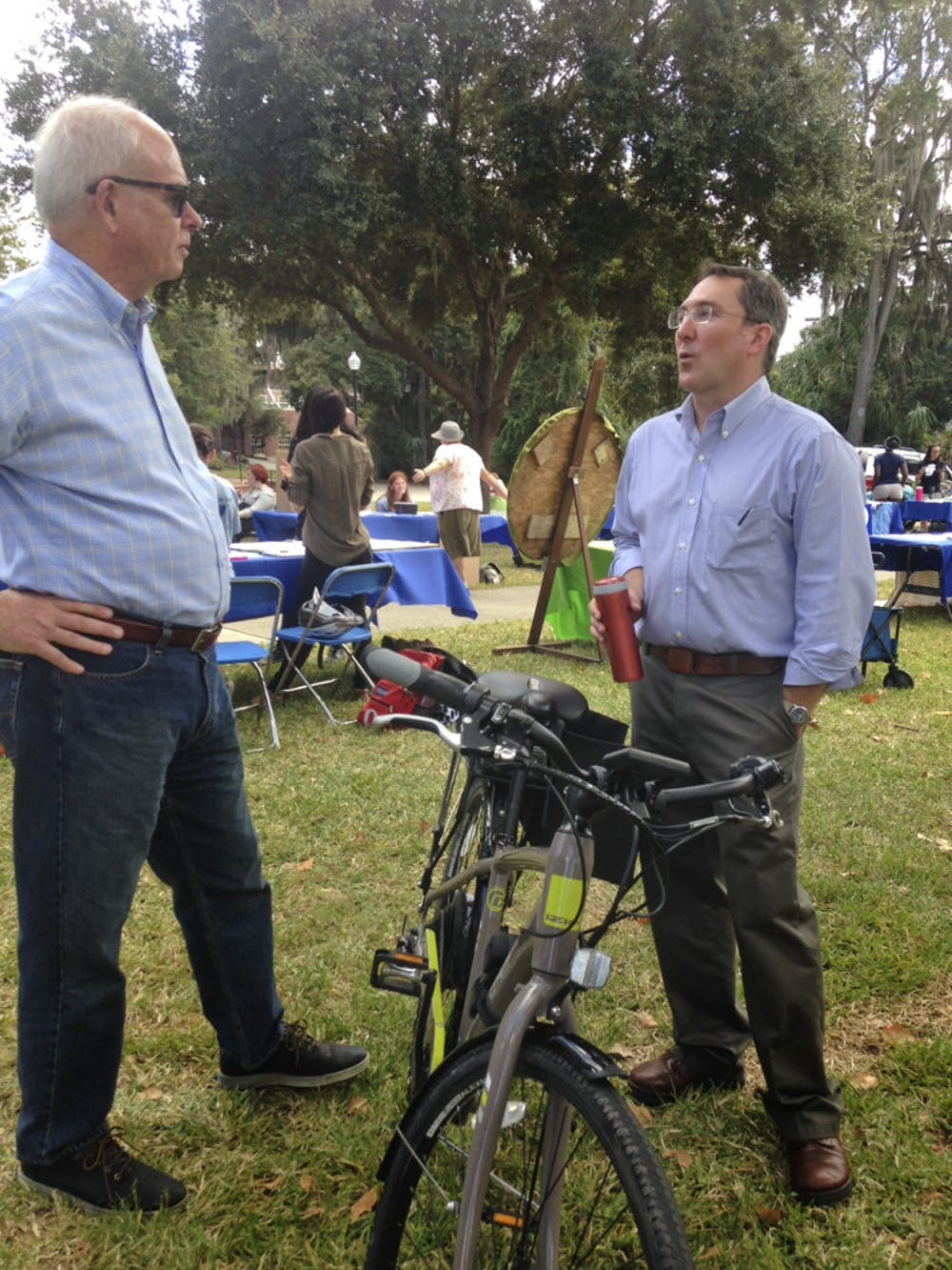 """<p>Former UF President Bernie Machen (left) converses with Matthew Williams, UF Office of Sustainability &amp; Energy Integration director, about his electric bike at the Sustainable Transportation Fair on the Reitz Union Lawn on Oct. 21, 2015. Williams said e-biking is """"the fastest, easiest and most pleasant way to get around campus.""""</p>"""