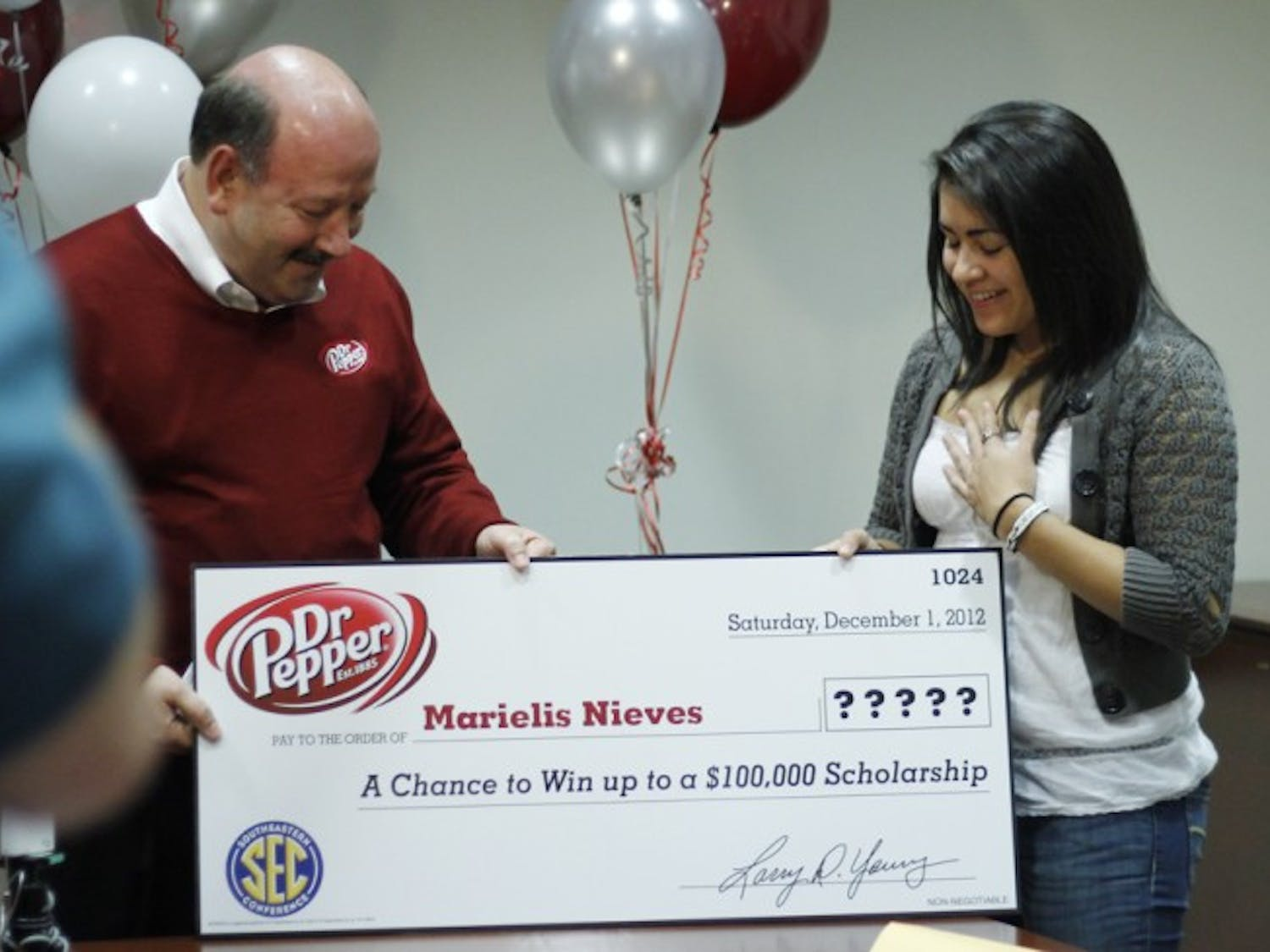 Chief marketing officer for Dr. Pepper Jim Trebilcock, left, presents Marielis Nieves, 18, of Saint Marys, Ga., with a check for $2,500 from her video entry in the Dr. Pepper Tuition Giveaway.