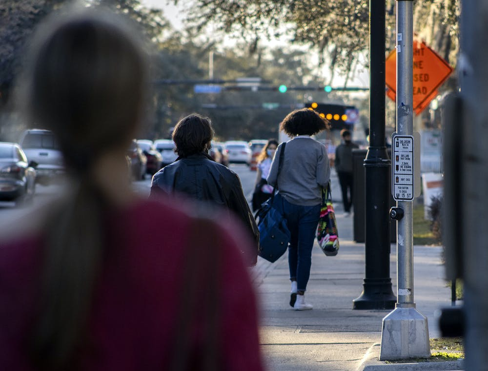 <p>Pedestrians walk down West University Avenue on Wednesday, Feb. 3, 2021. Signs down the road redirect traffic due to ongoing construction on the road, near UF campus and Midtown.</p>