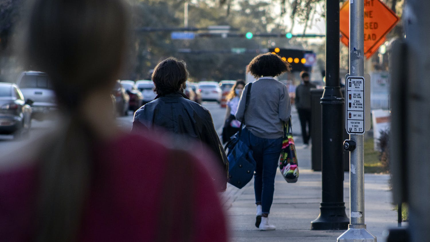 Pedestrians walk down West University Avenue on Wednesday, Feb. 3, 2021. Signs down the road redirect traffic due to ongoing construction on the road, near UF campus and Midtown.