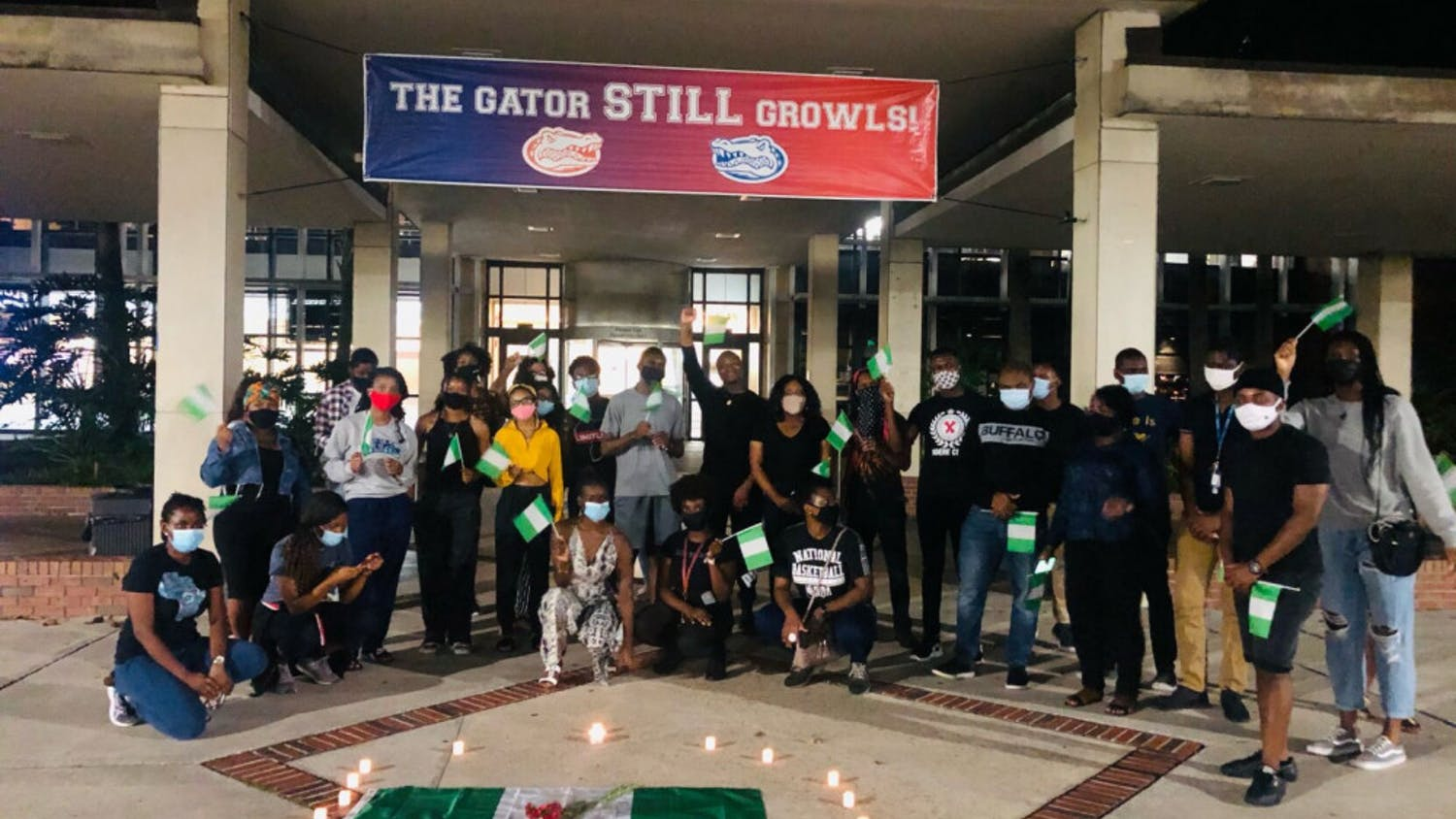 Masked UF students with Nigerian flags in hand stand in solidarity against police brutality in Nigeria and other forms of injustice throughout the continent.