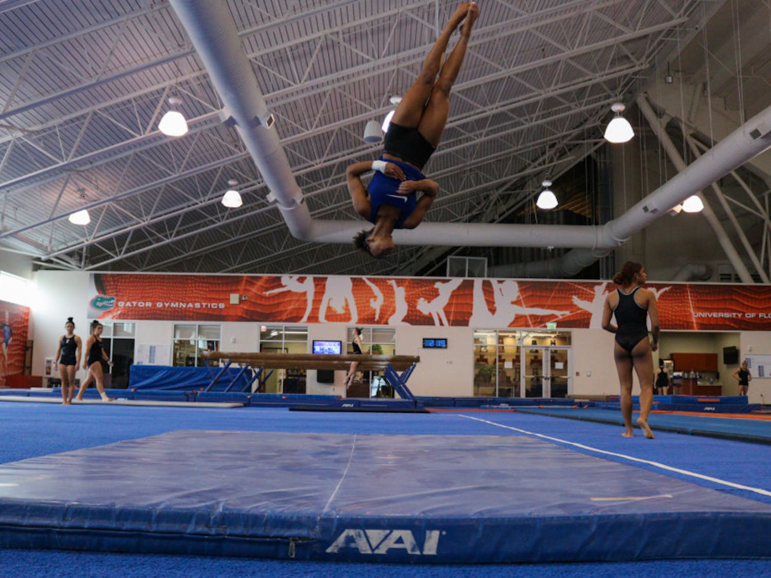 Thomas practices her flips and landings for her floor routine alongside a teammate.