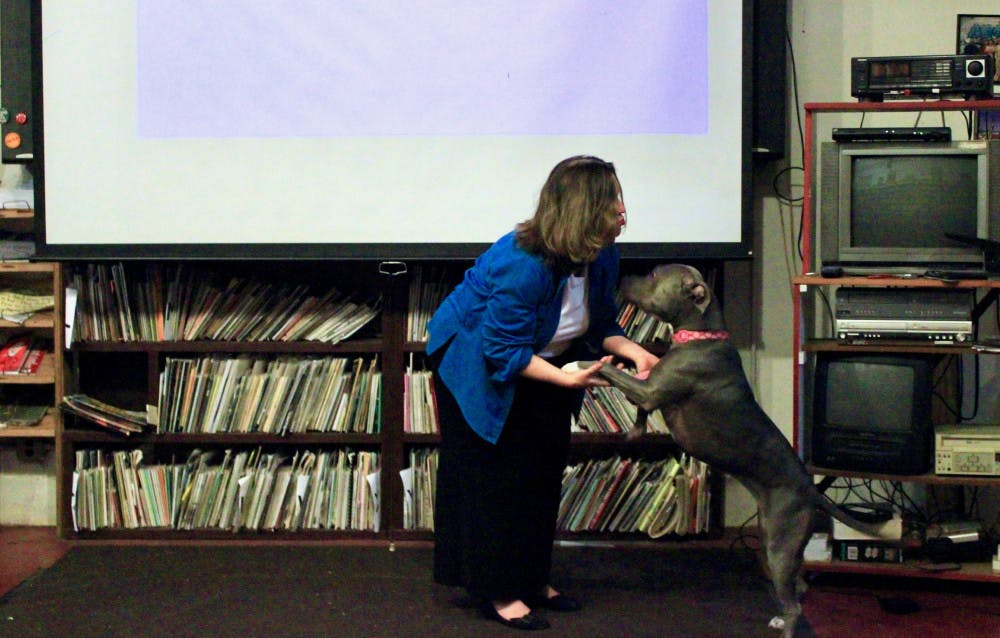 """<p dir=""""ltr""""><span>Lori, a support dog, greets Marcy LaHart, a Micanopy-based animal law lawyer, during her speech at the Civic Media Center in downtown Gainesville Tuesday evening.</span></p><p><span></span></p>"""