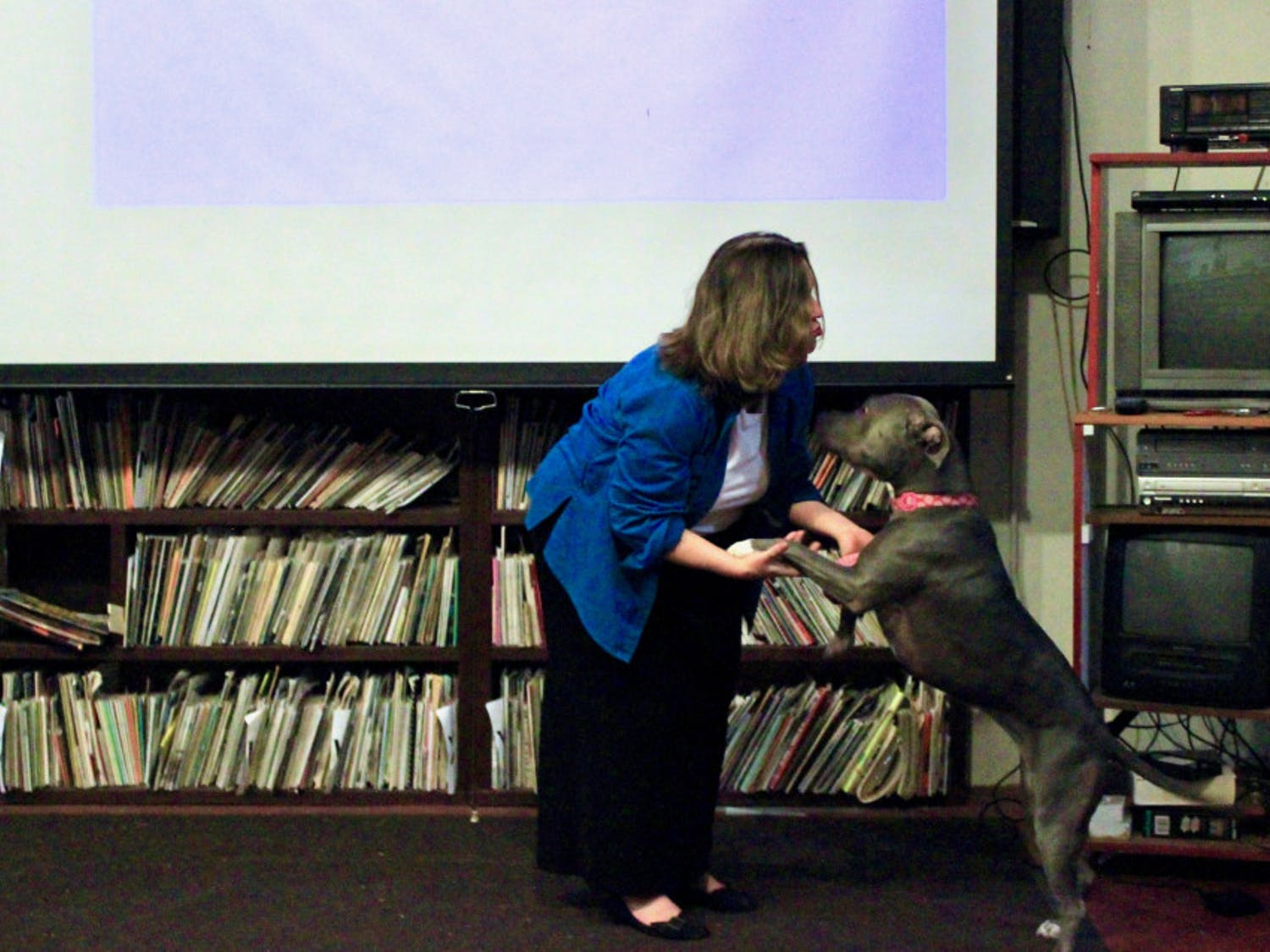 Lori, a support dog, greets Marcy LaHart, a Micanopy-based animal law lawyer, during her speech at the Civic Media Center in downtown Gainesville Tuesday evening.