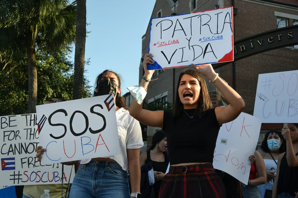 """<p>Marian Hernandez, 21, a psychology senior, (right), and Jenna Hidalgo, 21, a criminology and psychology senior, (left), shout """"Patria y Vida"""" as they raise signs embellished with colors of the Cuban flag on Friday, July 16, 2021. UF students gathered at the corner of University Avenue and 13th street to protest human rights abuses in Cuba.</p>"""