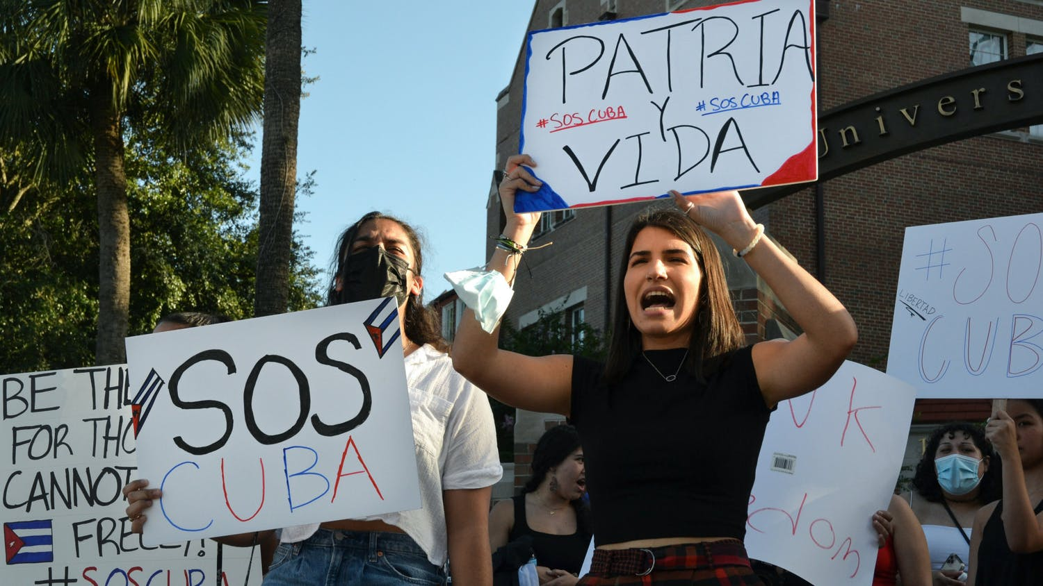 """Marian Hernandez, 21, a psychology senior, (right), and Jenna Hidalgo, 21, a criminology and psychology senior, (left), shout """"Patria y Vida"""" as they raise signs embellished with colors of the Cuban flag on Friday, July 16, 2021. UF students gathered at the corner of University Avenue and 13th street to protest human rights abuses in Cuba."""