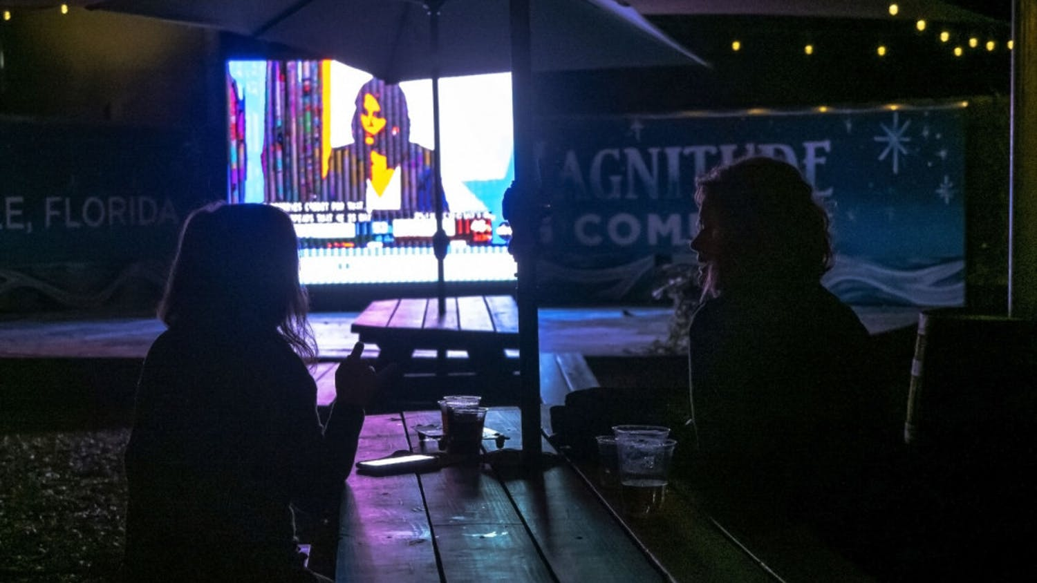 Two women watch the presidential election results at First Magnitude Brewery, located in Gainesville, Fla., on Tuesday, Nov. 3, 2020.