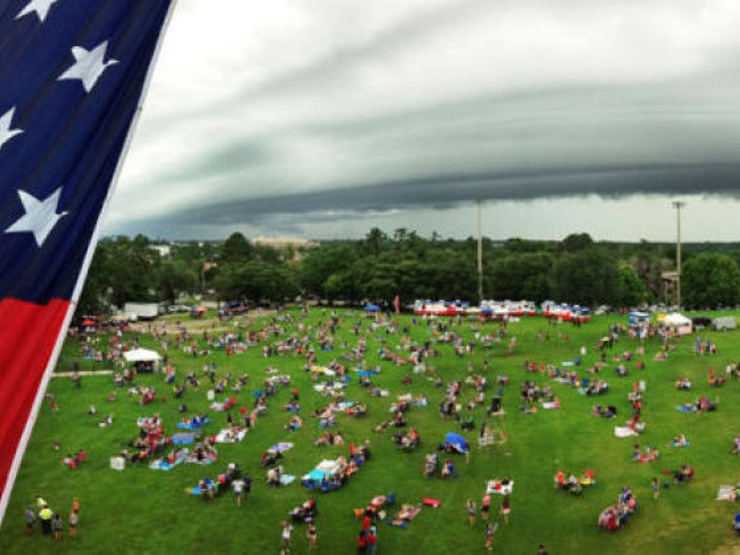 In a panoramic photo, a crowd of students and residents gathers beneath an impending storm on campus at Flavet Field for UF's Fanfares & Fireworks event in 2013.