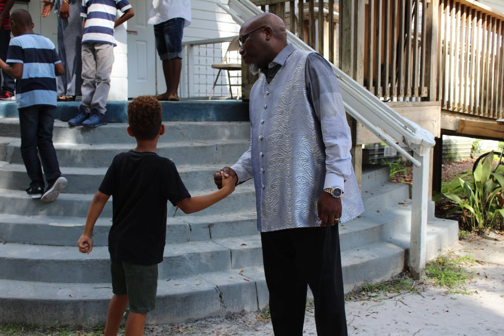 "<p><span id=""docs-internal-guid-1e1f75cd-1803-7b13-bdab-e797edad3804""><span>Chris Stokes greets a young churchgoer on Sunday outside the New Beginning Christian Worship Center in Micanopy. About 20 children attended the service.</span></span></p>"