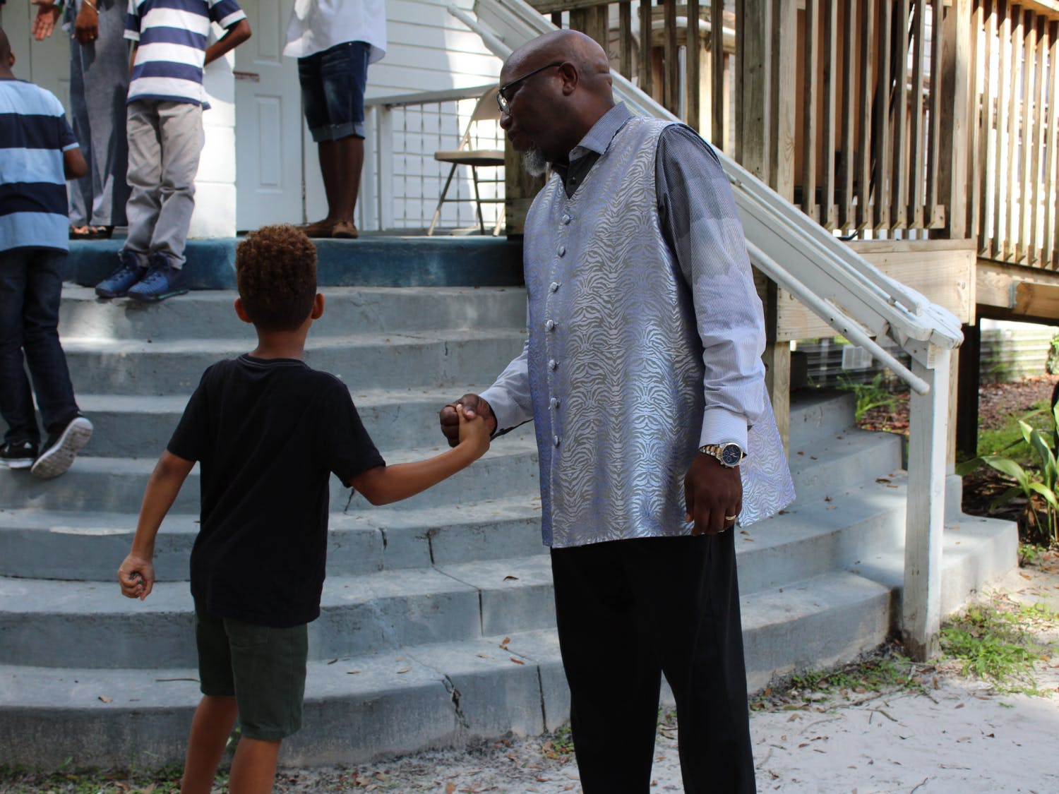 Chris Stokes greets a young churchgoer on Sunday outside the New Beginning Christian Worship Center in Micanopy. About 20 children attended the service.