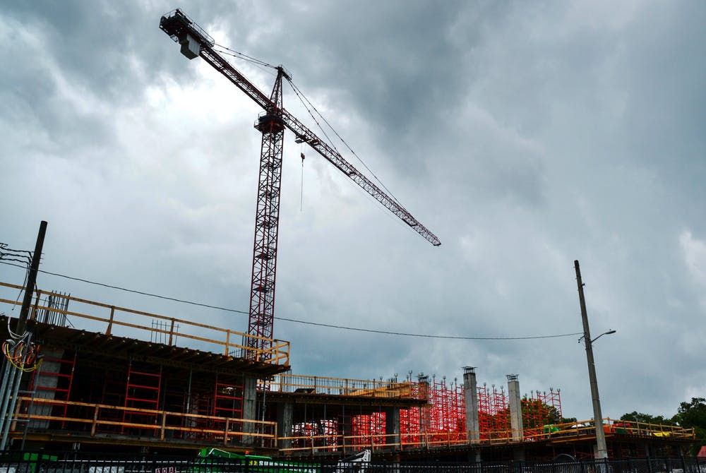 A crane towers over the Evolve apartment complex construction site at 931 West University Avenue on Tuesday, June 16, 2021. Evolve is one of several new mid-rise apartment complexes under construction in midtown and downtown Gainesville.