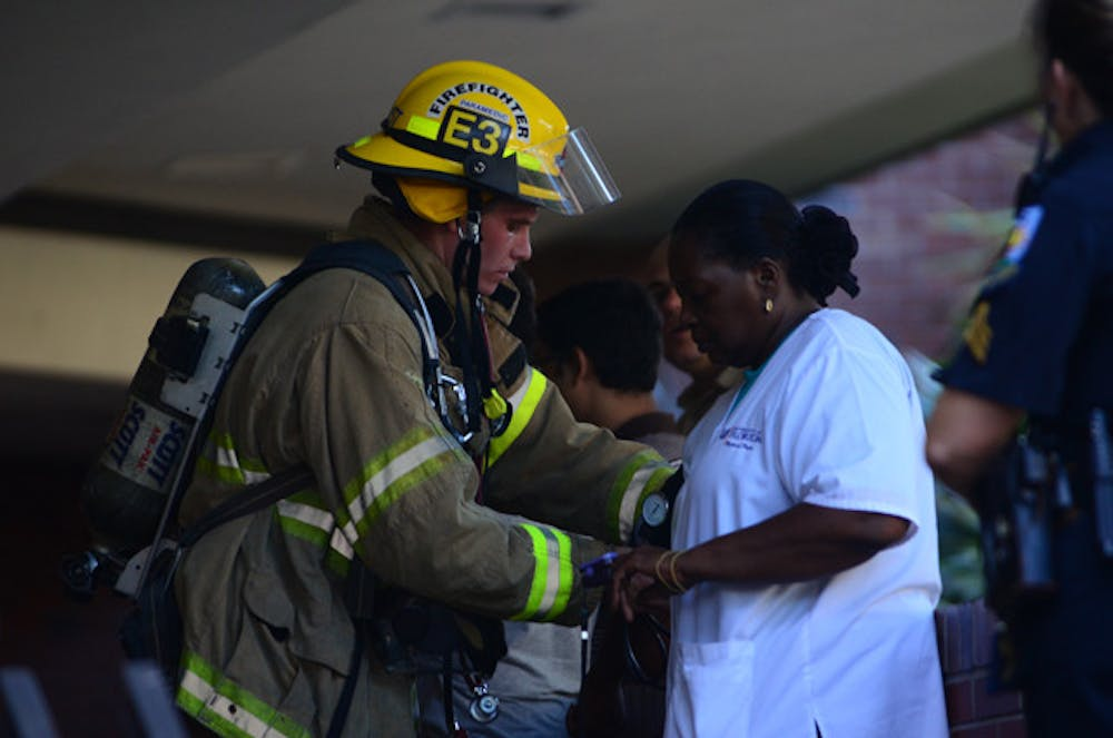 <p>Gainesville firefighter/paramedic Matt Pfost checks the blood pressure of UF employee Stephanie Bennett-White in Turlington after the building was evacuated because of a chemical spill on Monday afternoon.</p>