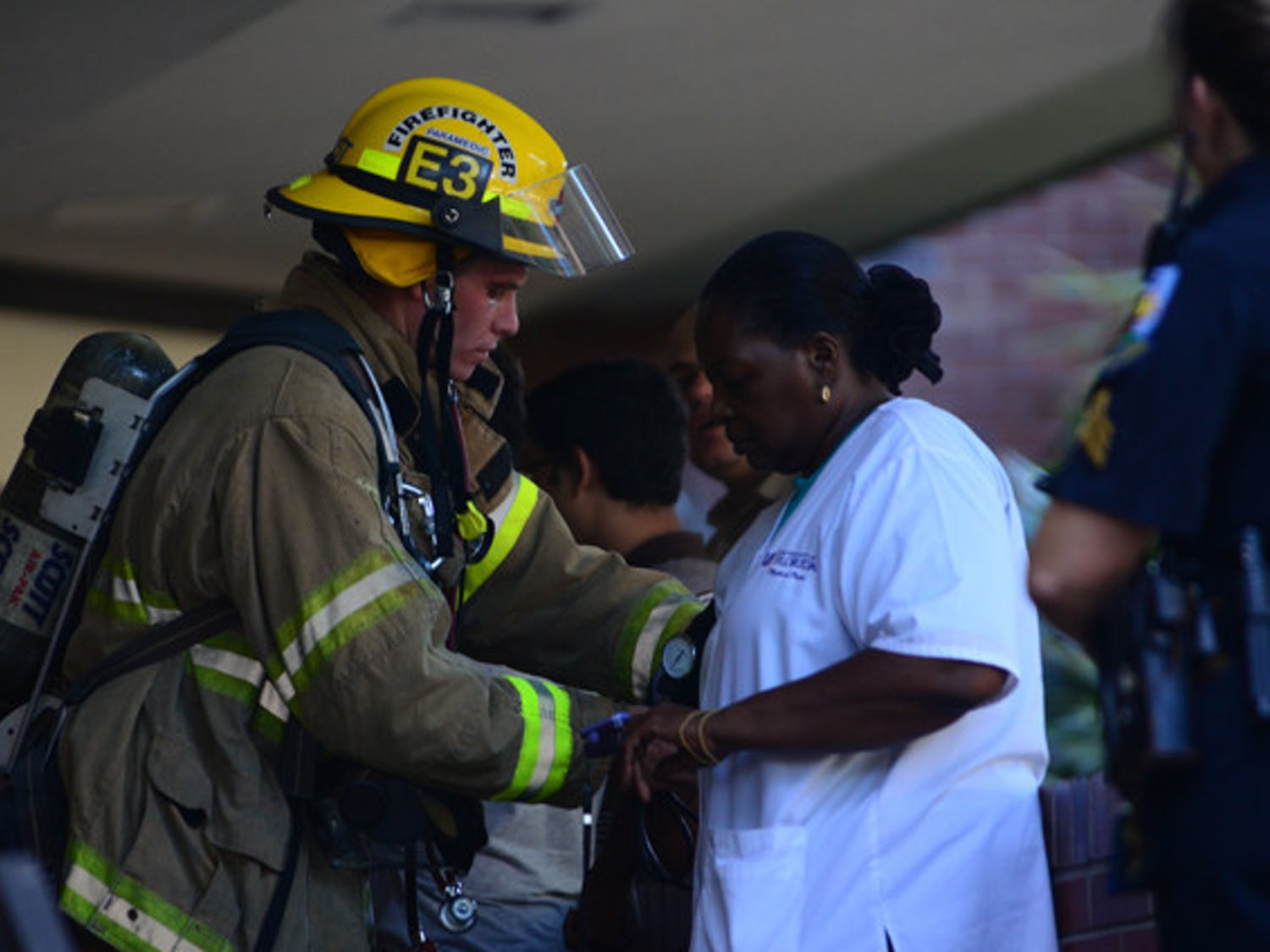 Gainesville firefighter/paramedic Matt Pfost checks the blood pressure of UF employee Stephanie Bennett-White in Turlington after the building was evacuated because of a chemical spill on Monday afternoon.