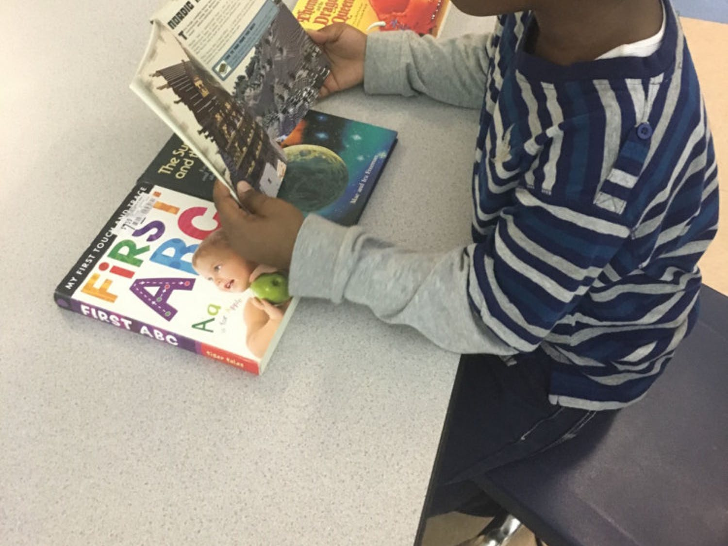 "Seven-year-old Jakhari McFadden admires the Nordic Hall design in his new ""Minecraft: Essential Handbook."" The second-grader and every student at Sidney Lanier Elementary School now has access to free books with the school's new book house, which was unveiled at about 11 a.m. Tuesday in the cafeteria."
