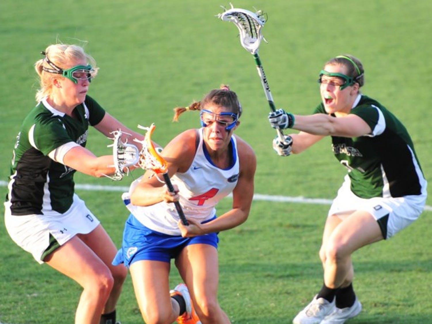 Florida attacker Kitty Cullen splits two Dartmouth defenders while attacking the goal during the Gators' 20-4 win against the Big Green on Tuesday. Cullen scored five goals.