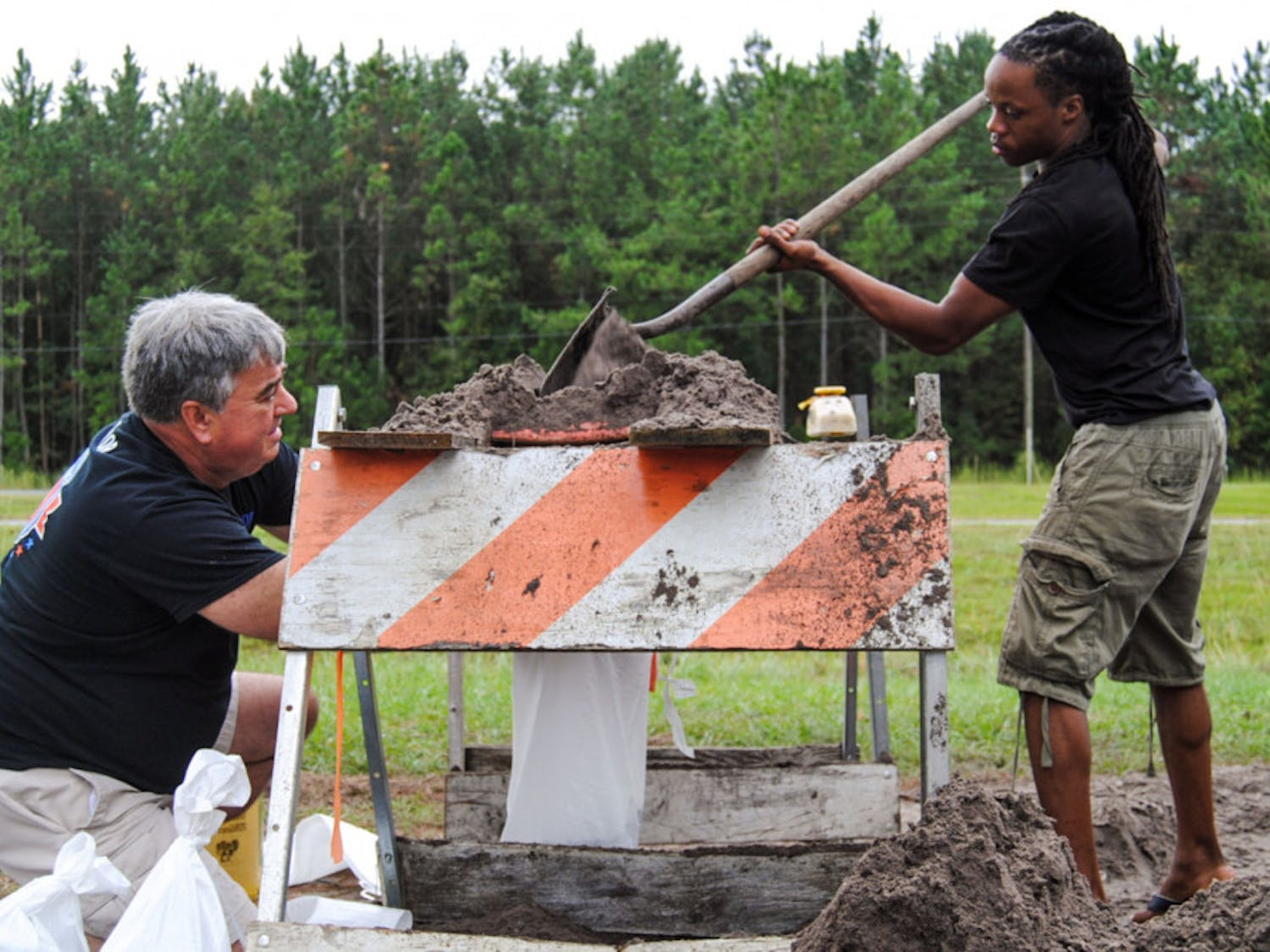 """From left: Gainesville residents Erich Marzolf, 55, and Michael Haynes, 26, help each other make sandbags at the Alachua County Public Works Department's sandbag location, located at 11855 NW U.S. Highway 441, on Thursday morning. The men are strangers, but they are both working to prepare for possible Hurricane Matthew water buildup. """"See if I can protect the front of my house,"""" Marzolf said. """"We don't have gutters."""""""