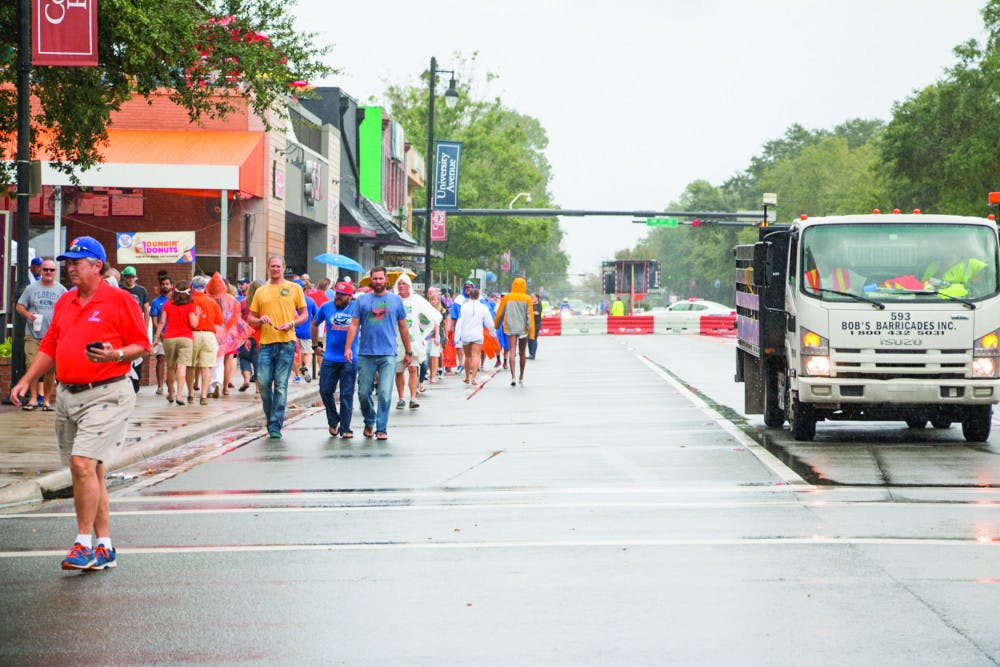 "<p dir=""ltr"">Despite the rain, fans walk down the closed-off University Avenue to Ben Hill Griffin Stadium on Saturday afternoon for the UF Homecoming football game.</p>"