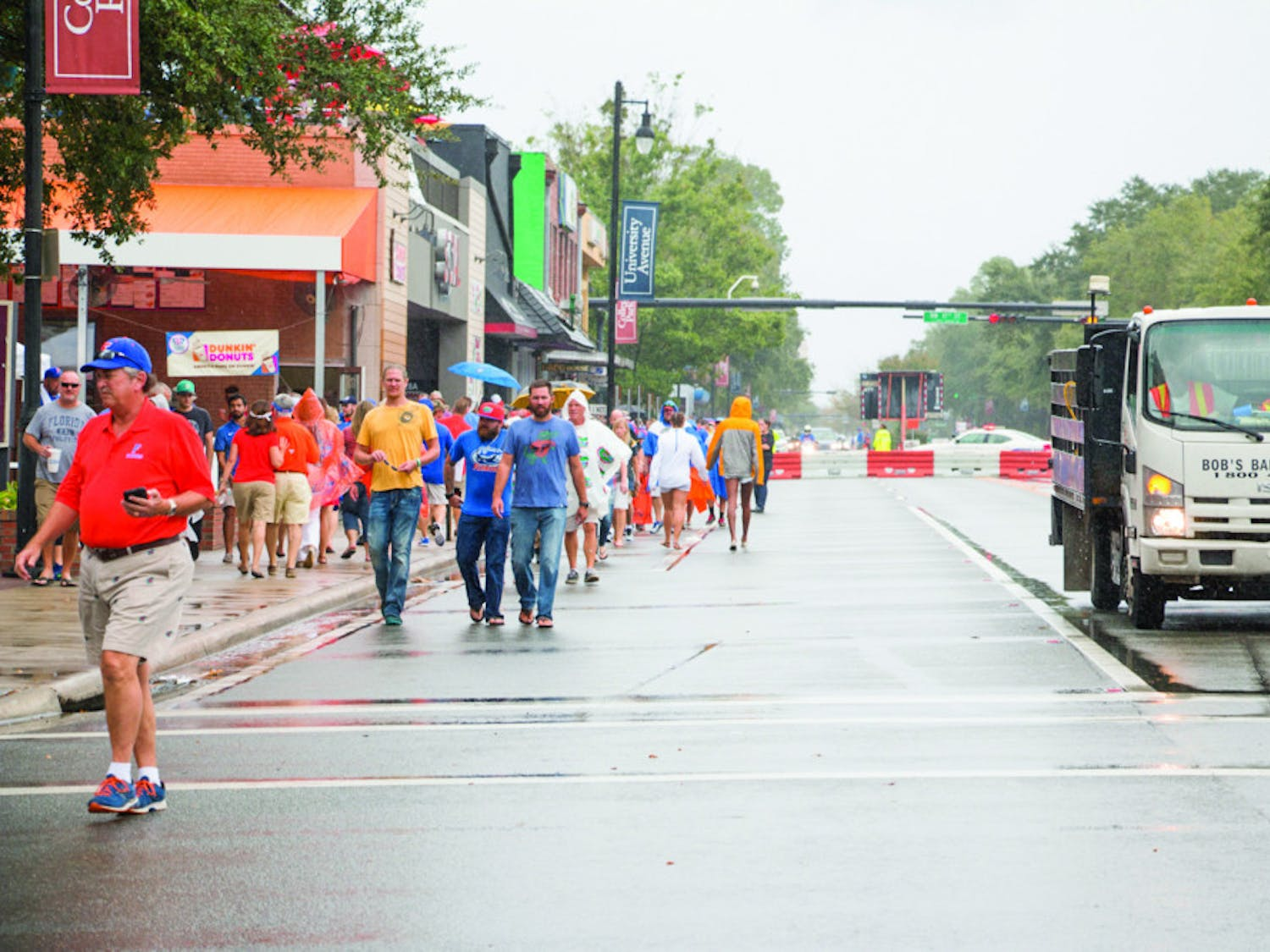 Despite the rain, fans walk down the closed-off University Avenue to Ben Hill Griffin Stadium on Saturday afternoon for the UF Homecoming football game.