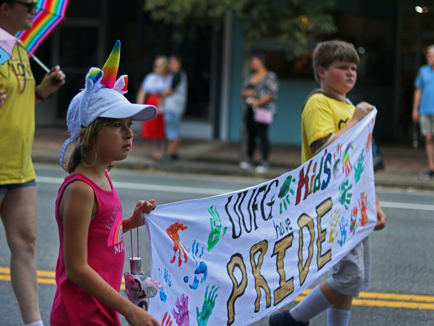 Children from the Unitarian Universalist Fellowship of Gainesville hold a banner while marching in the parade on Saturday afternoon.