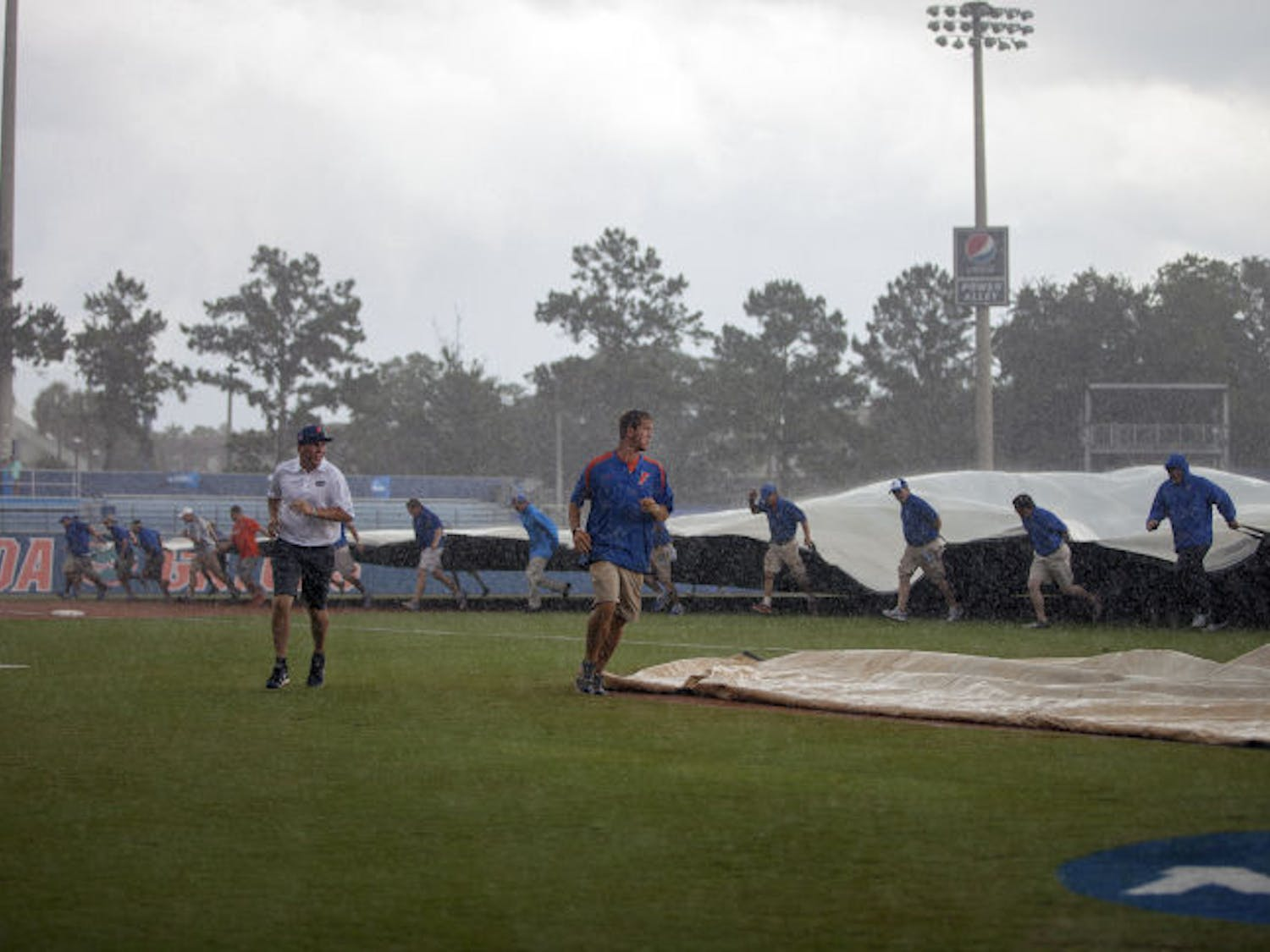 Members of Florida's grounds crew place a tarp over the infield during the rain delay in UF's 5-2 loss to UNC on Saturday at McKethan Stadium. The Tar Heels scored all five of their runs in the inning following the rain delay, which lasted more than three hours.
