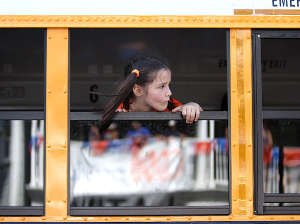 <p>A girl stares out the window of an Alachua County school bus on West University Avenue.</p>