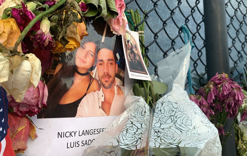 """A photo of Nicole """"Nicky"""" Langesfeld and Luis Sadovnic hangs on a memorial wall in Surfside, Florida on Saturday, July 3, 2021. Langesfeld and Sadovnic are two UF alumni among the more than 100 people still unaccounted for after the partial collapse of the Champlain Towers South building on June 24."""