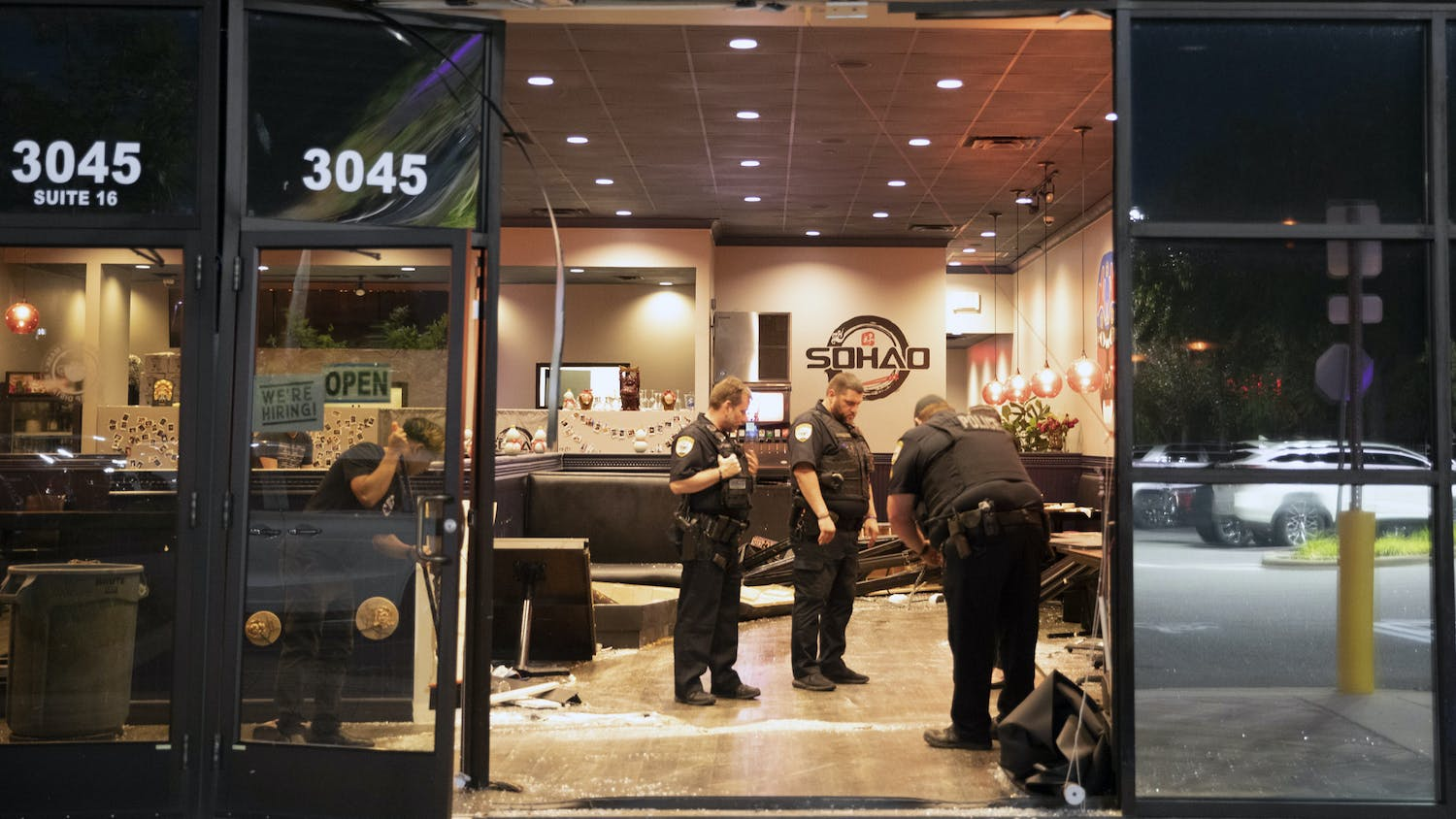 Police officers investigate the area and help clean broken glass from the floor of SOHAO Cafe & Gator Suyaki after a blue Dodge was driven through the front of the restaurant on Monday, May 17, 2021.