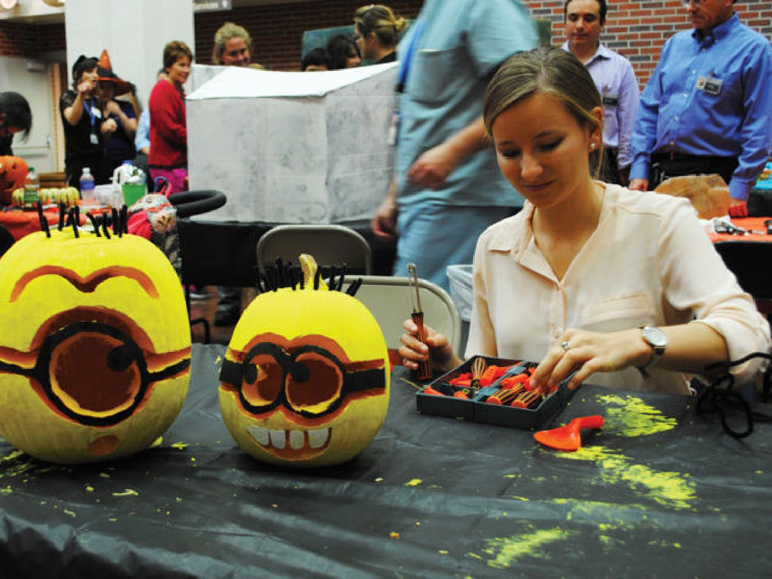 """UF architecture junior Michelle Hook, 21, makes """"Despicable Me"""" minions at the 31st Annual Pumpkin Carve-Off and carnival for patients at UF Health Shands Children's Hospital on Monday."""