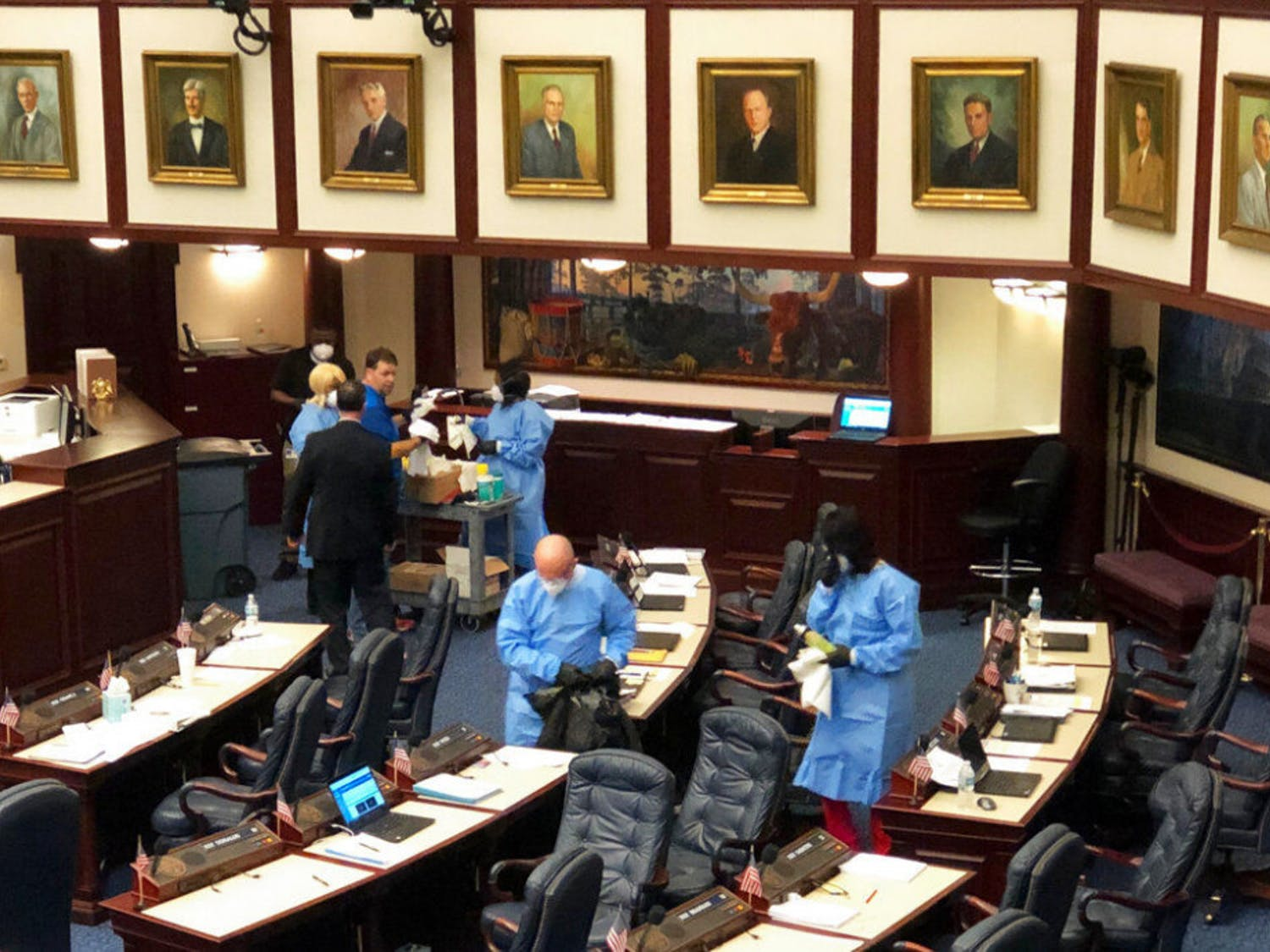 Crew members swab down Florida's House floor at the state Capitol in Tallahassee, Fla., Monday, March 9, 2020, after several members voluntarily submitted themselves for testing of a new strain of coronavirus. The Florida House abruptly recessed Monday afternoon and cleared public galleries after several of its members agreed to be tested for the new strain of coronavirus after recently attending a political event in Washington where one attendee tested positive for COVID-19. (AP Photo/Bobby Caina Calvan)