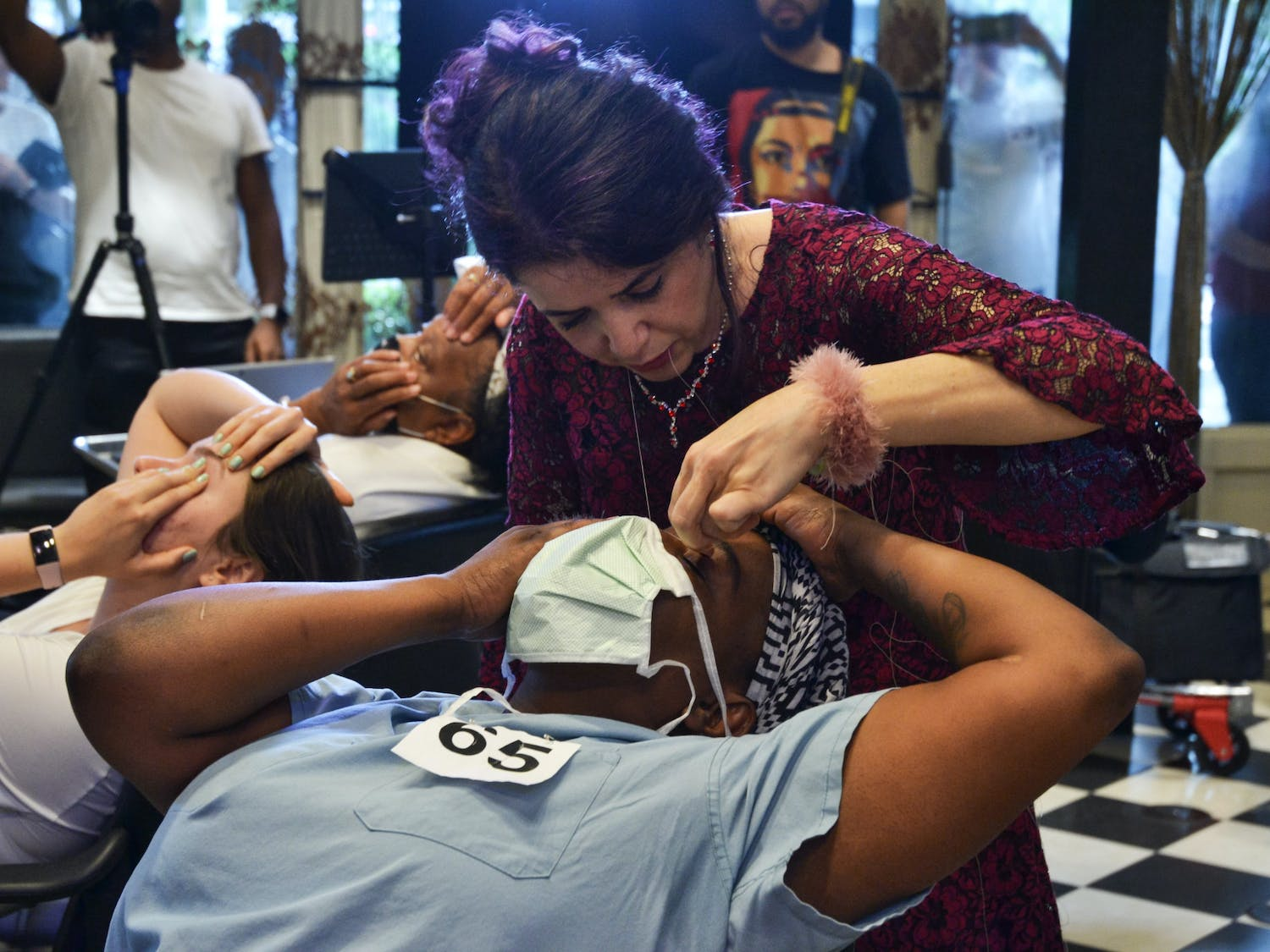 Ziba Ahmadi, owner of Salon Ziba in Gainesville, threads Shavonne Carter's eyebrows, and breaks the previous record for most eyebrows threaded by one person in one hour on Wednesday, June 16, 2021.