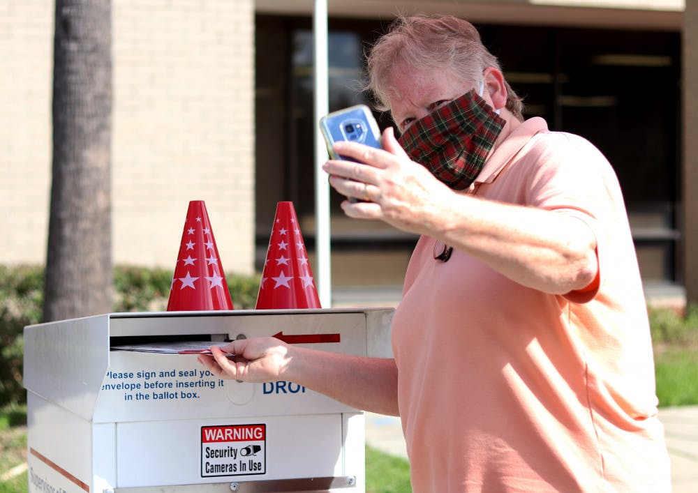 <p>Linda Spurny takes a selfie with her ballot as she drops it off in front of the Alachua County Supervisor of Elections Office on Thursday, Oct. 15, 2020. She said she took the photo to insure it is counted. (Lauren Witte/Alligator Staff)</p>