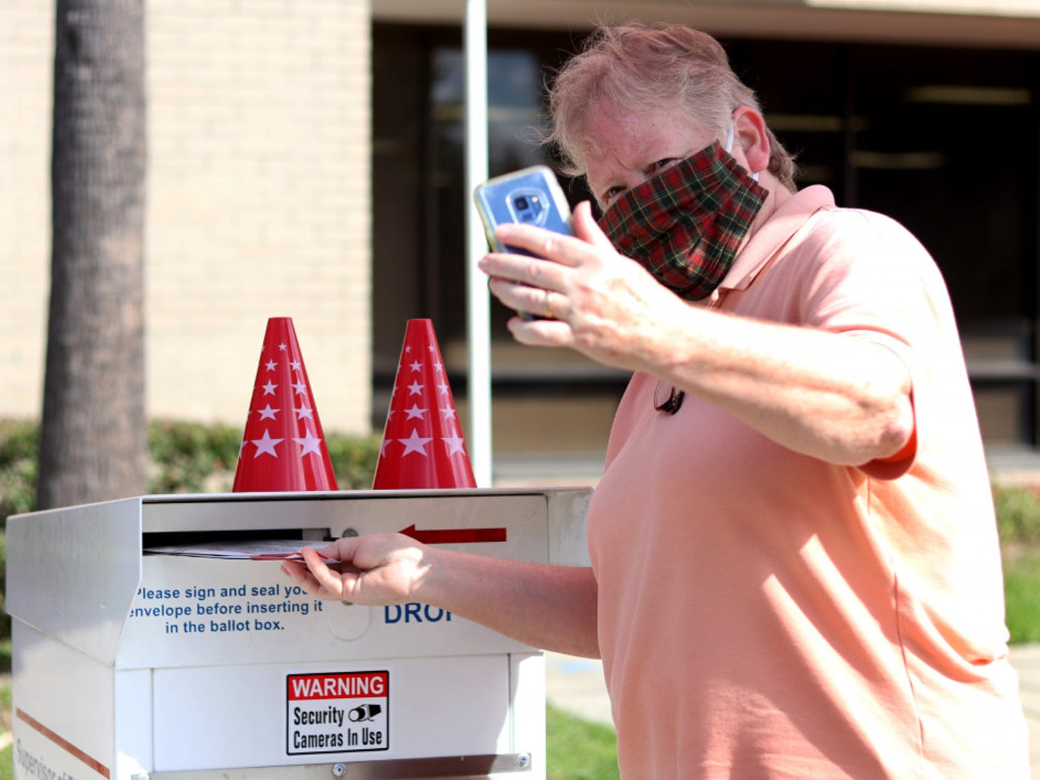 Linda Spurny takes a selfie with her ballot as she drops it off in front of the Alachua County Supervisor of Elections Office on Thursday, Oct. 15, 2020. She said she took the photo to insure it is counted. (Lauren Witte/Alligator Staff)