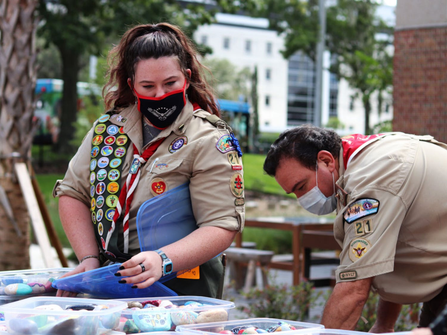 Olivia Foli, 16, an eagle scout who helped start Gainesville's first female troop, and her dad, Randy Foli, take some of the 676 painted healing stones out of its containers at the UF Health Children's Healing Garden on Friday, Sept. 18, 2020.