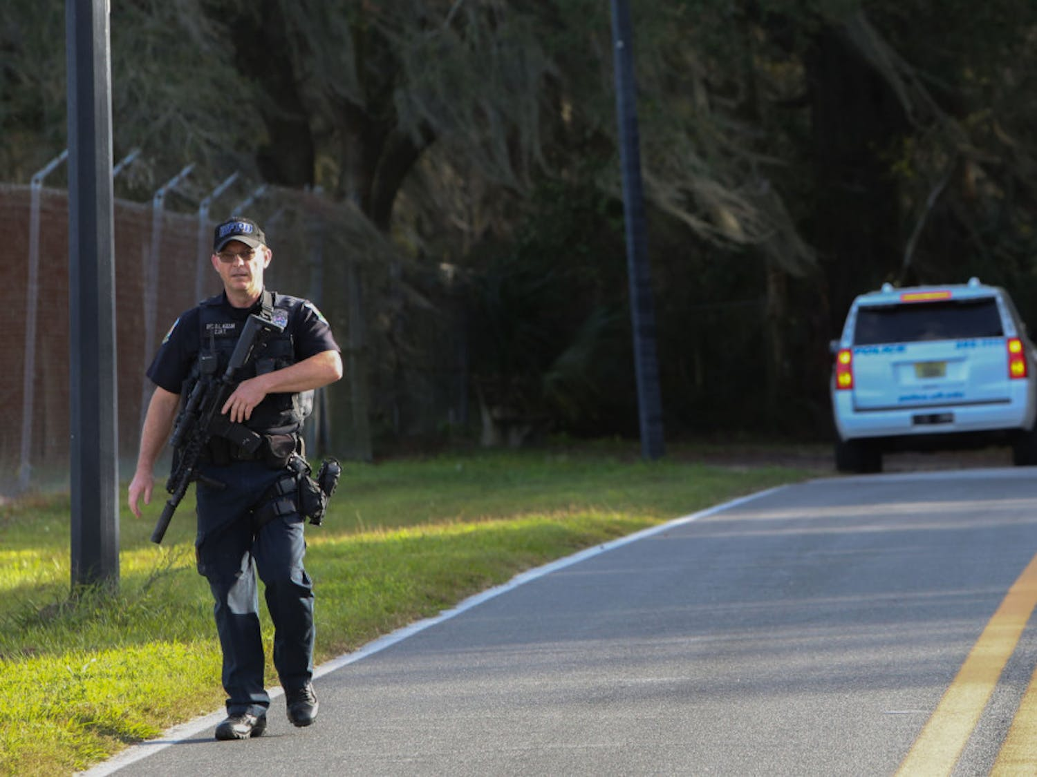 A University of Florida Police Department officer walks towards his vehicle Friday after searching a wooded area near the UF College of Veterinary Medicine for a suspect reportedly firing a gun at targets.